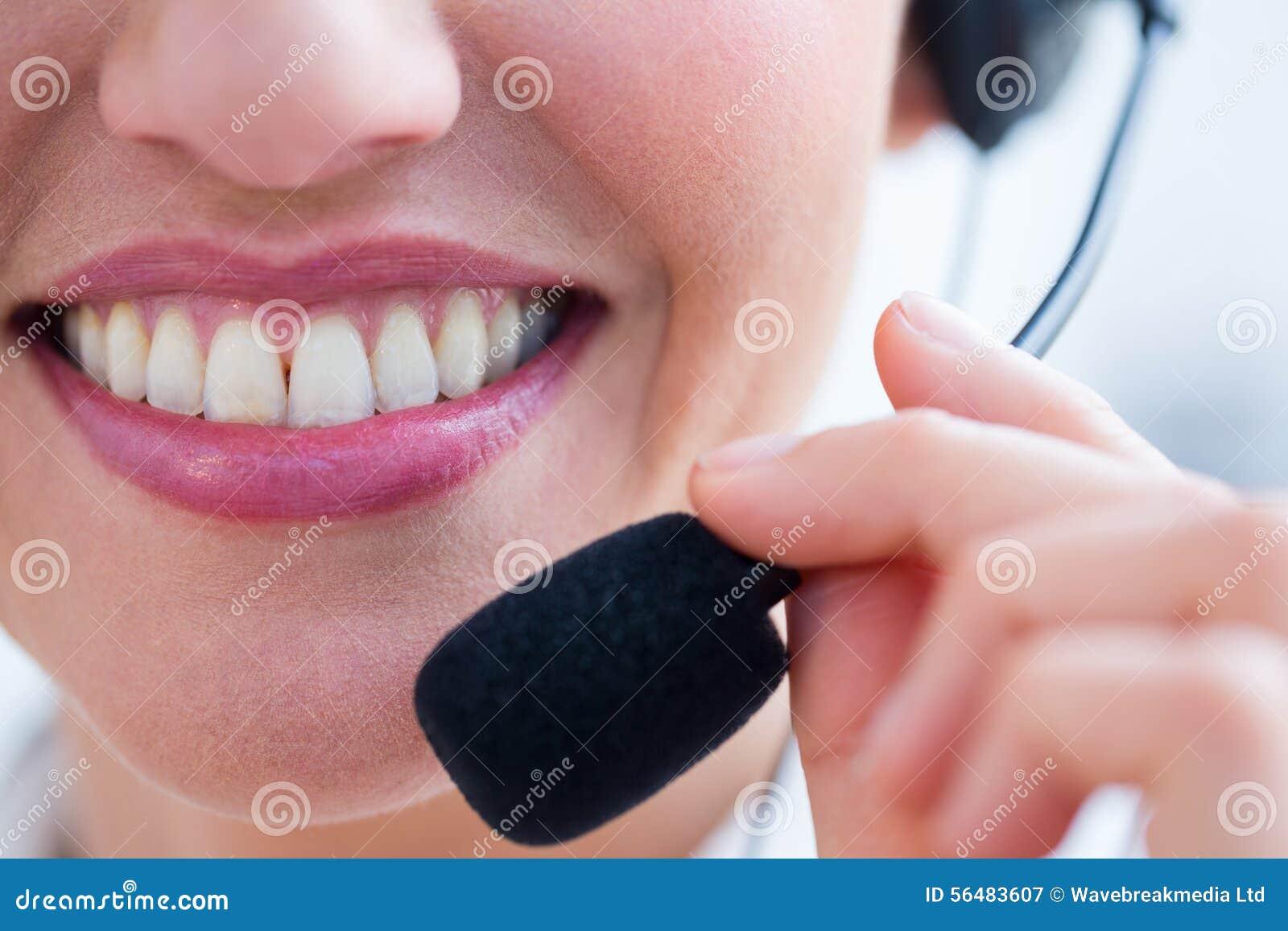 Sourire de la jolie brune utilisant l écouteur
