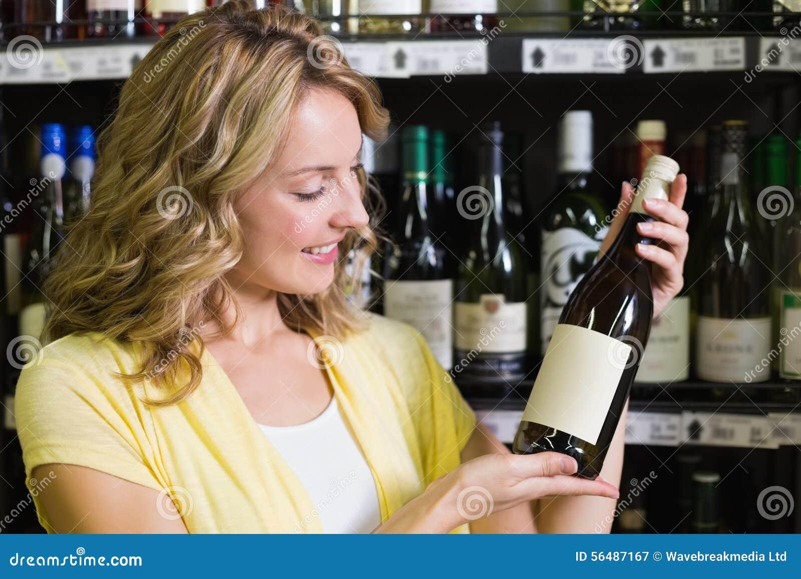 Sourire femme assez blonde montrant une bouteille de vin