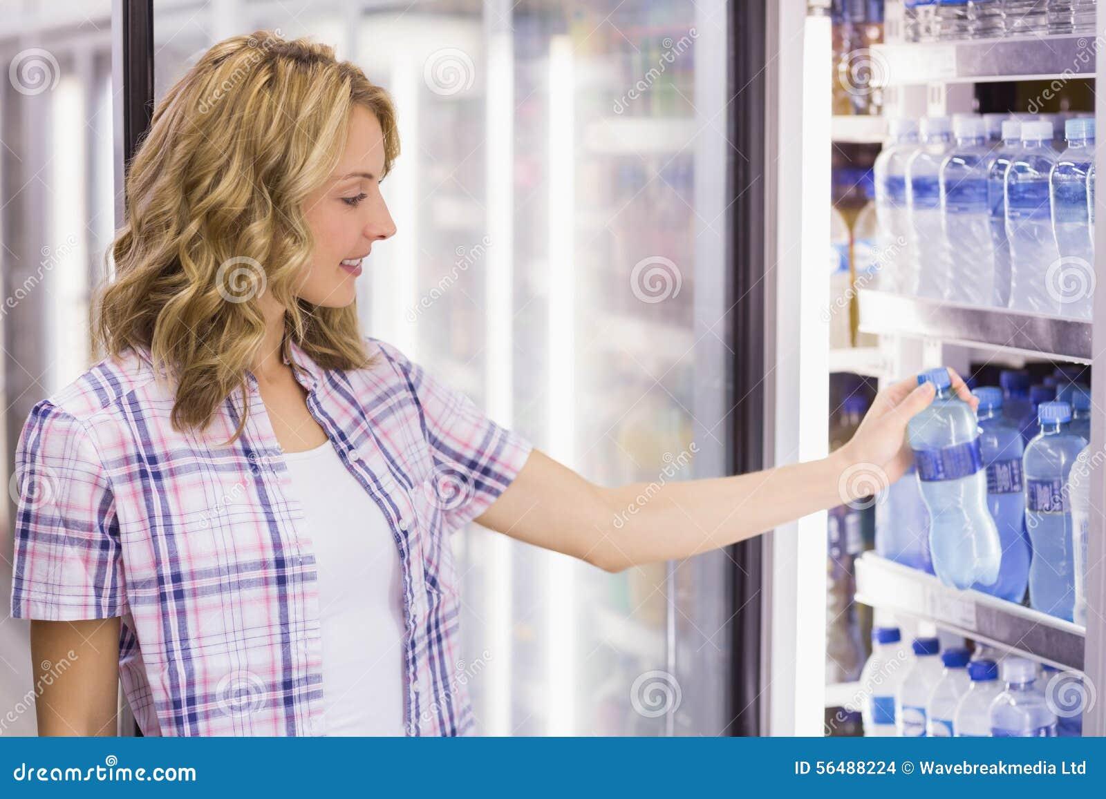 Sourire femme assez blonde prenant une bouteille d eau dans le supermarché