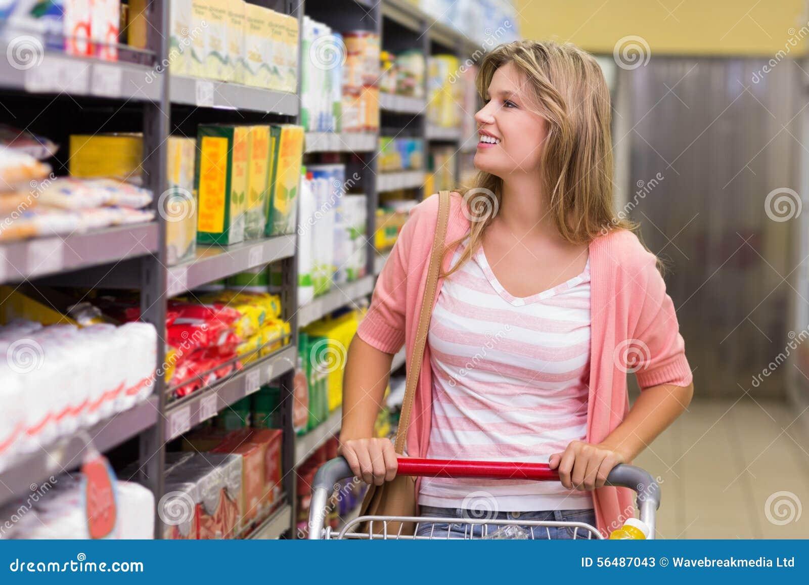 Sourire femme assez blonde regardant l étagère et achat produits