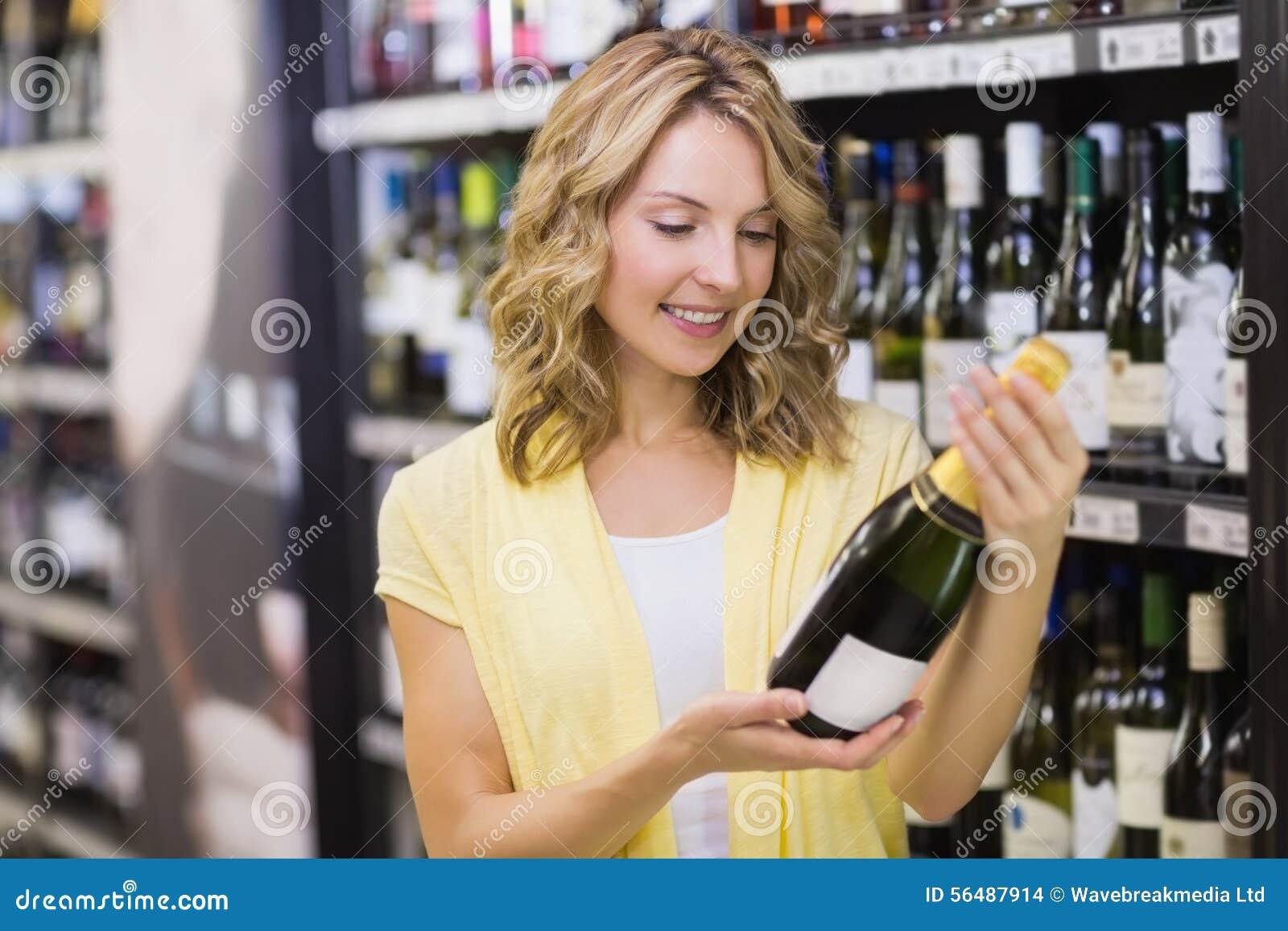 Sourire femme assez blonde regardant la bouteille de vin