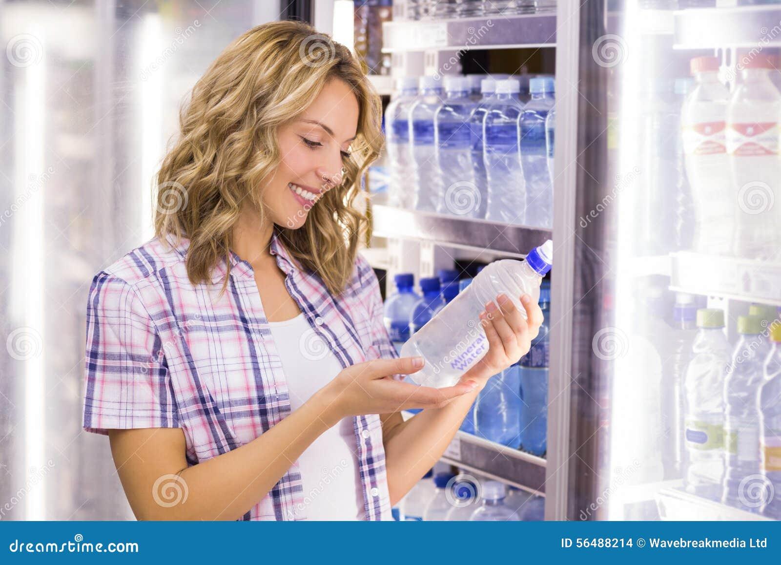 Sourire femme assez blonde regardant une bouteille d eau