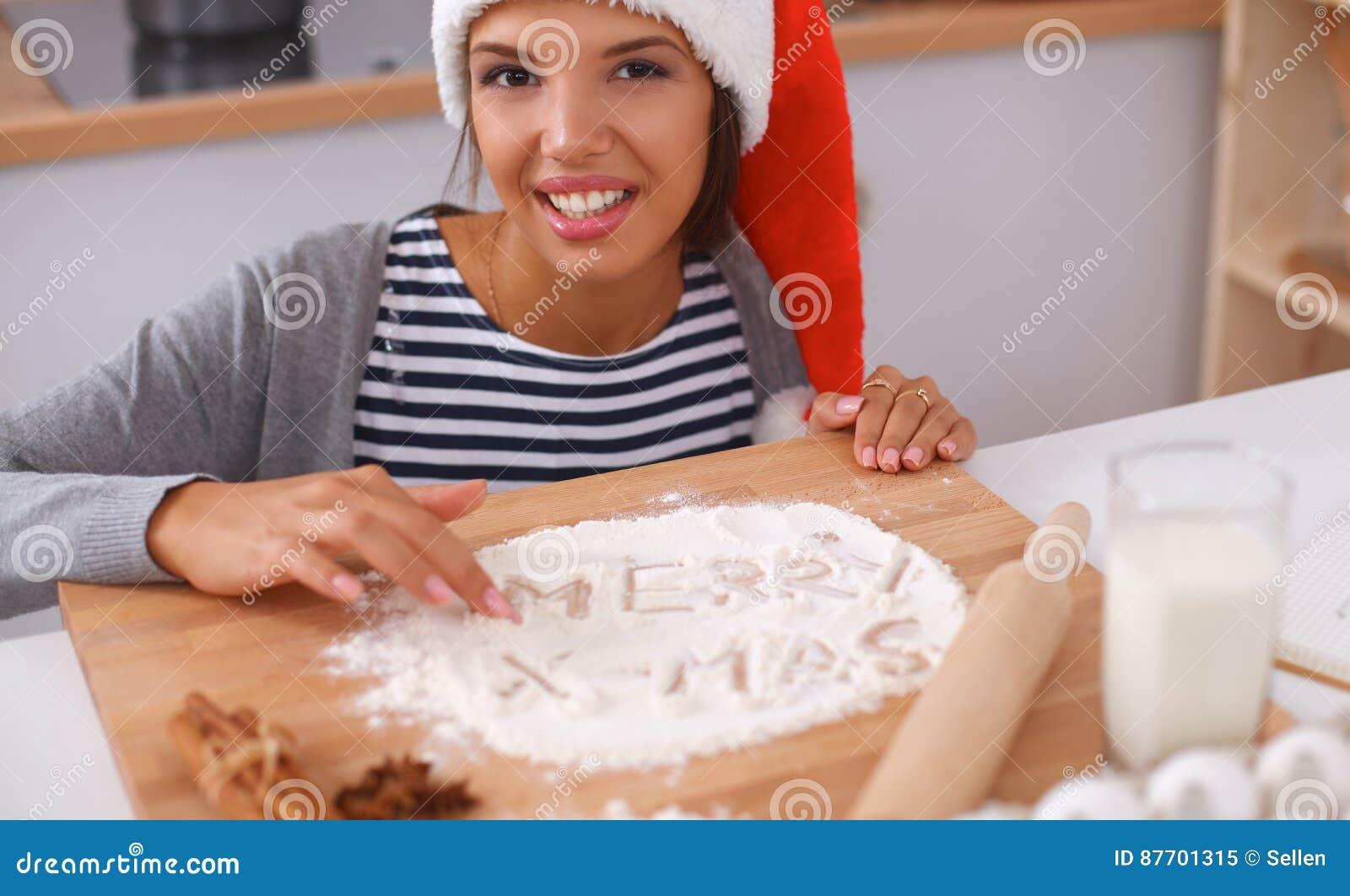 Sourire heureux de jeune femme heureux ayant l amusement avec des préparations de Noël utilisant le chapeau de Santa