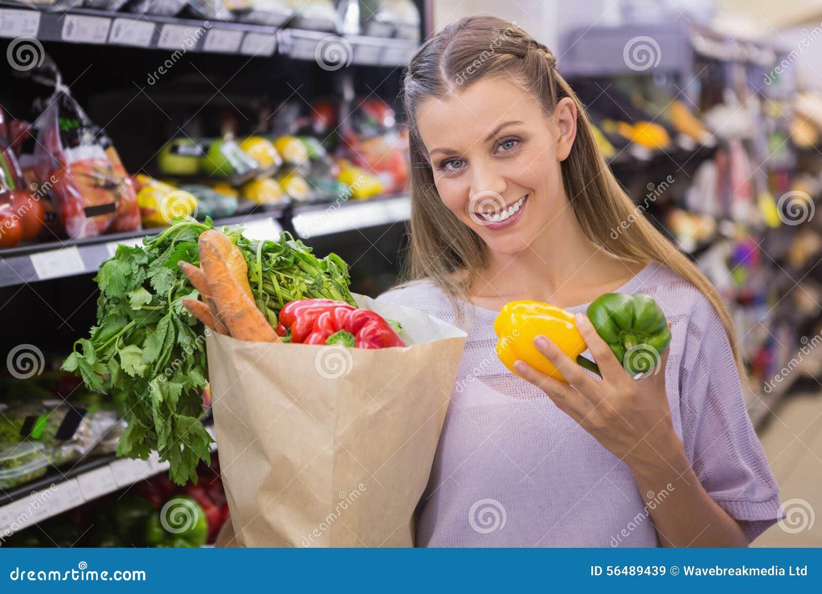 Sourire légumes de achat de femme assez blonde