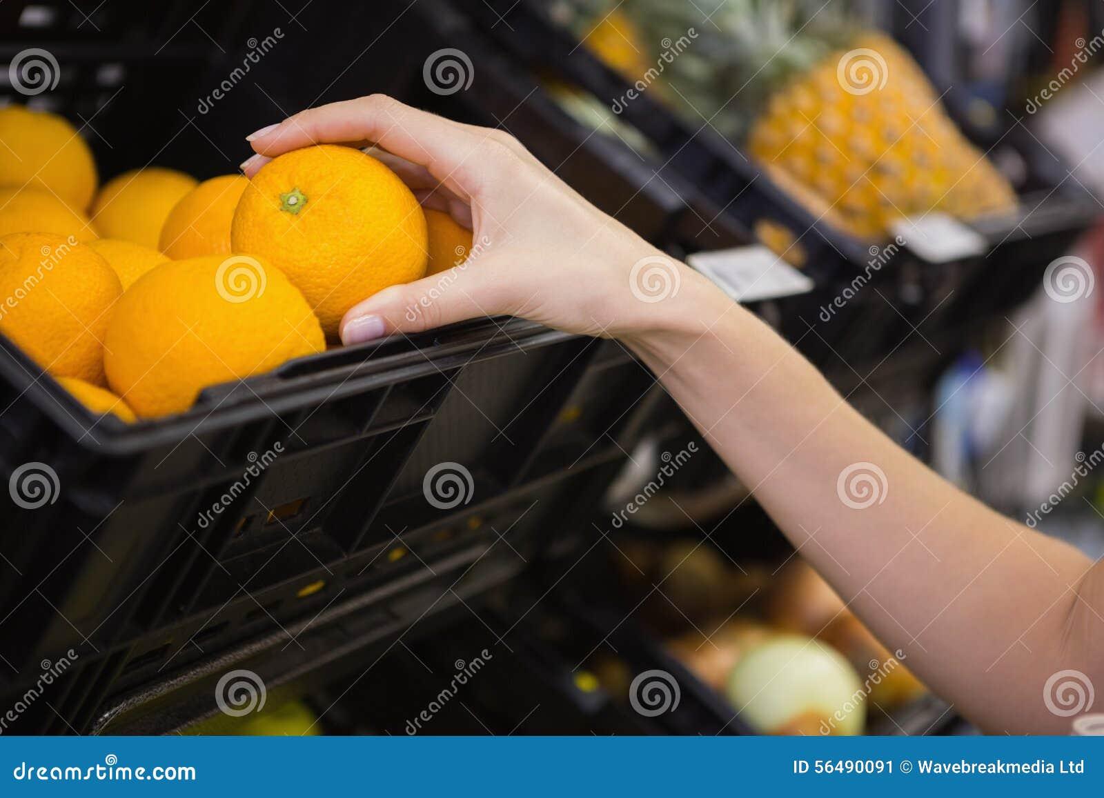 Sourire oranges de achat de femme assez blonde