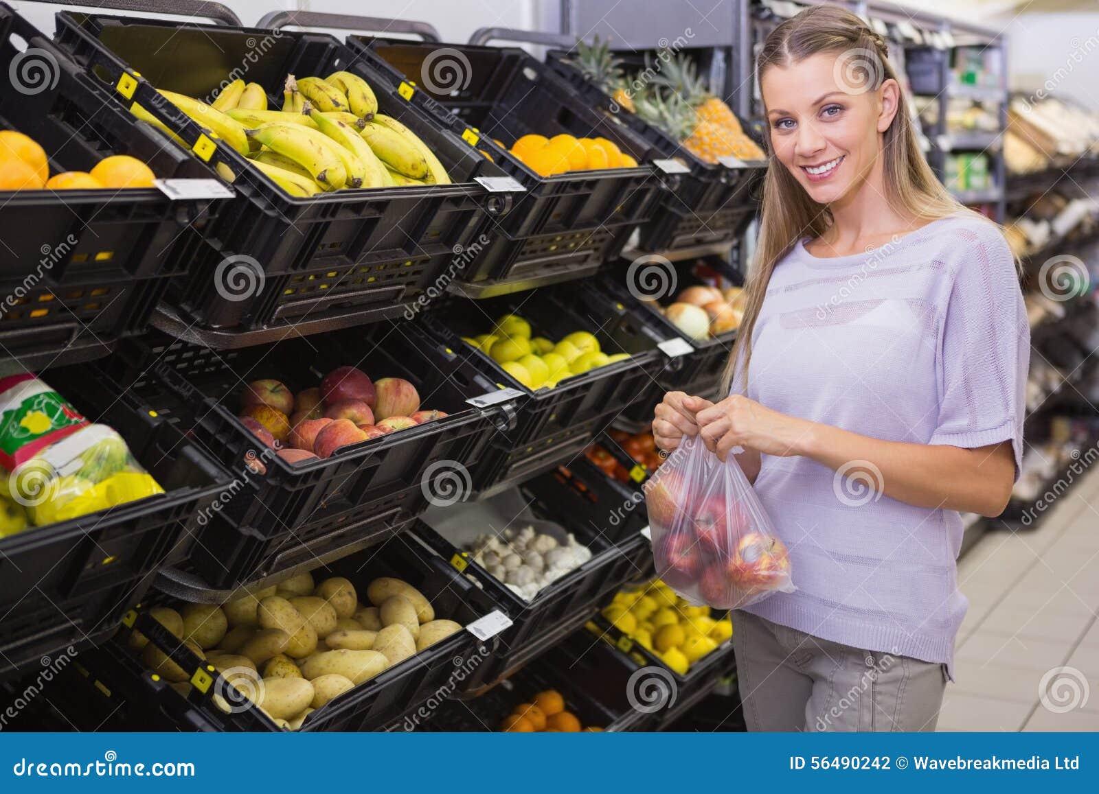 Sourire pommes de achat de femme assez blonde