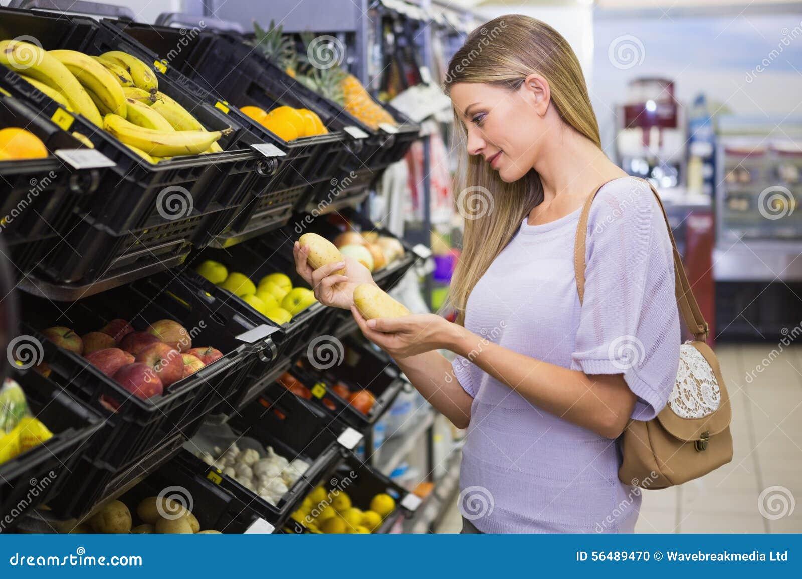 Sourire pommes de terre de achat de femme assez blonde