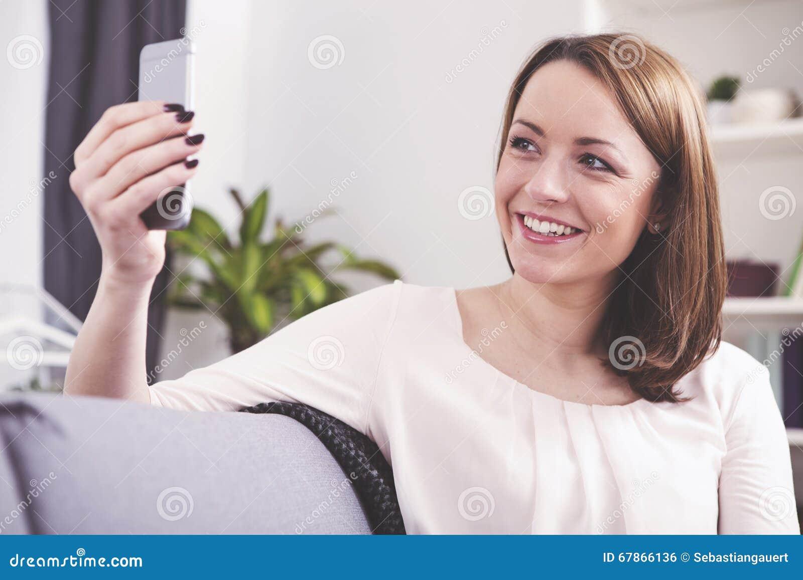 Sourire se reposant de fille d une chevelure brune heureuse sur un sofa