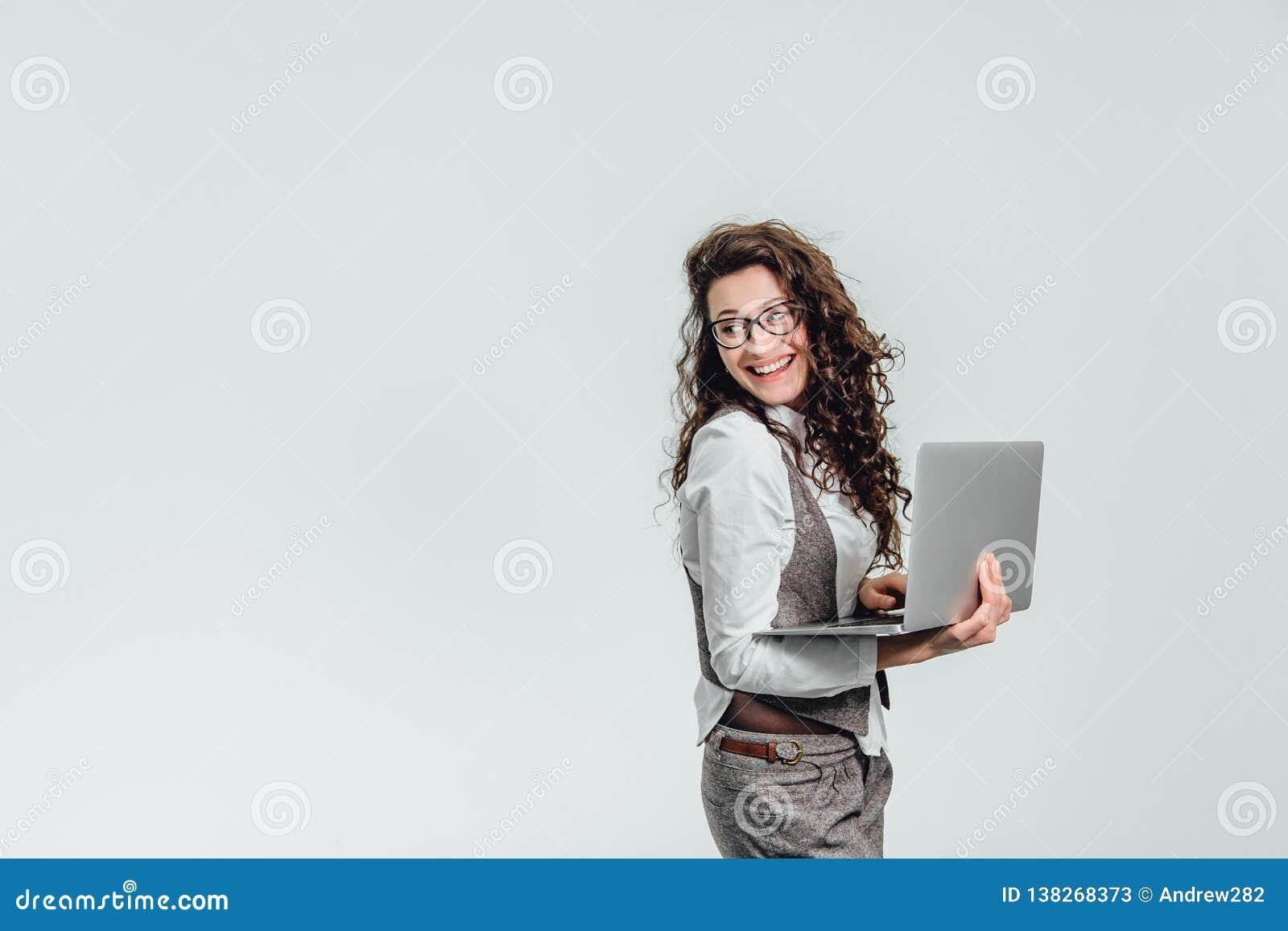 Sourires de jeune fille de BBeautiful Travaux sur un ordinateur portable dans les verres et une chemise blanche