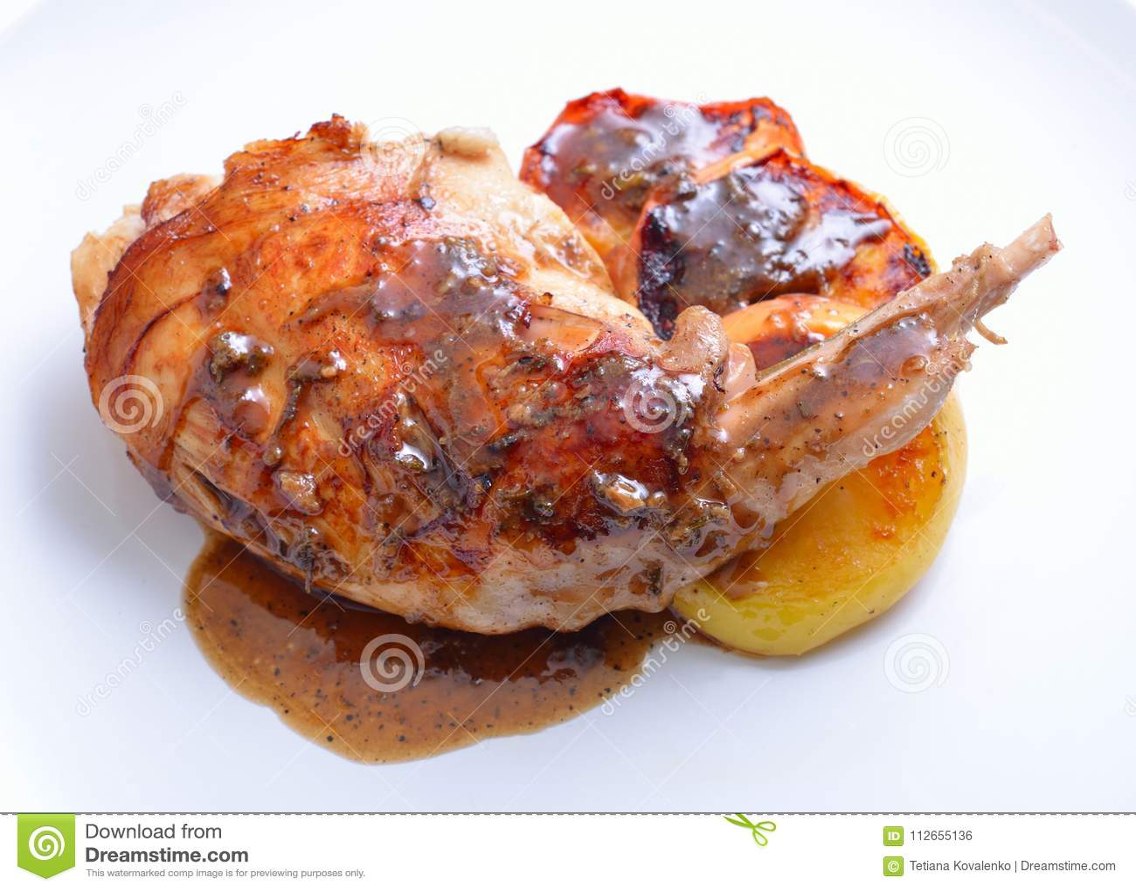Sous Vide兔子腿用在白色板材的sous和烤苹果