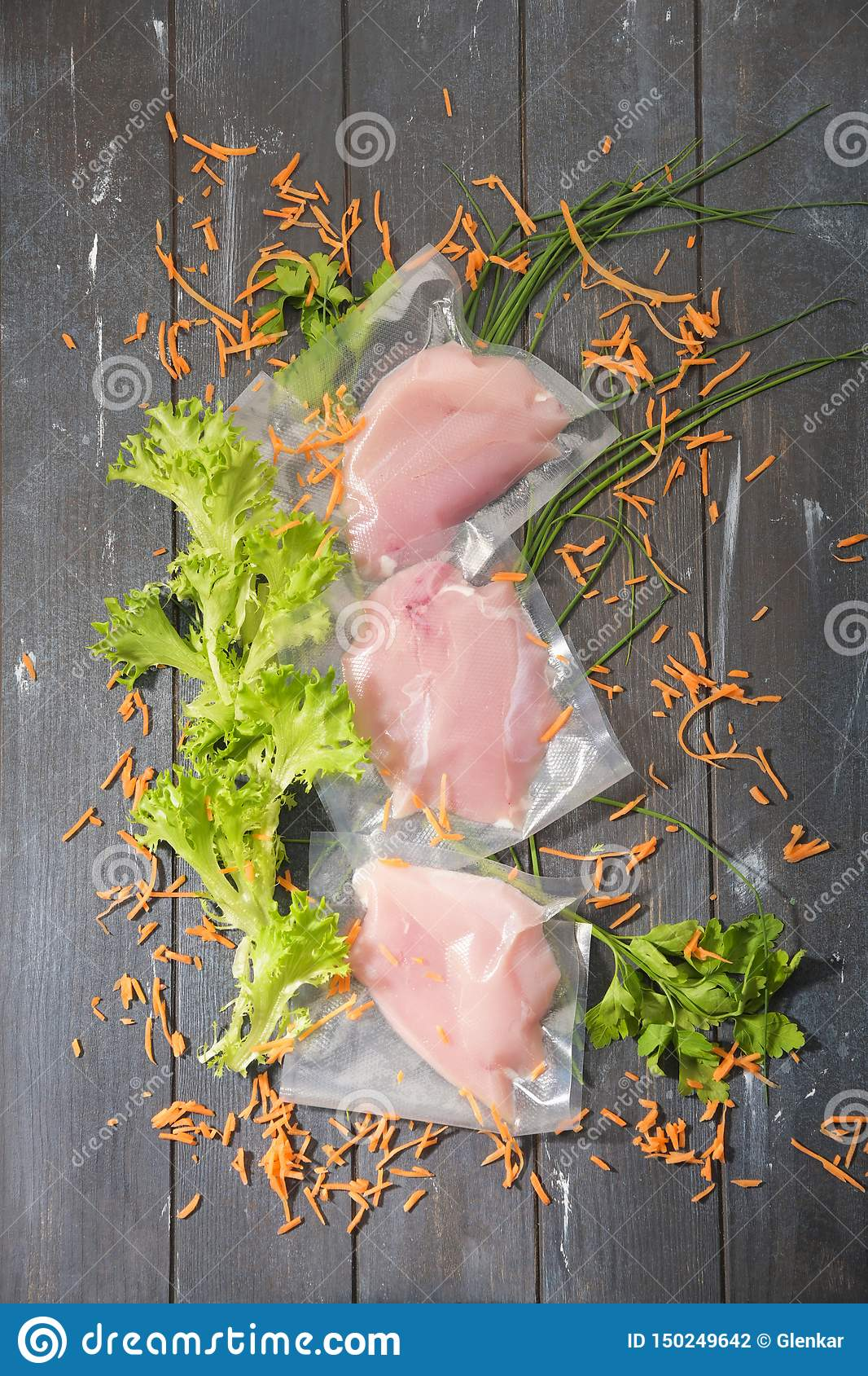 Sous Vide cooking concept. Vacuum packed ingredients arranged on wooden dyed background.
