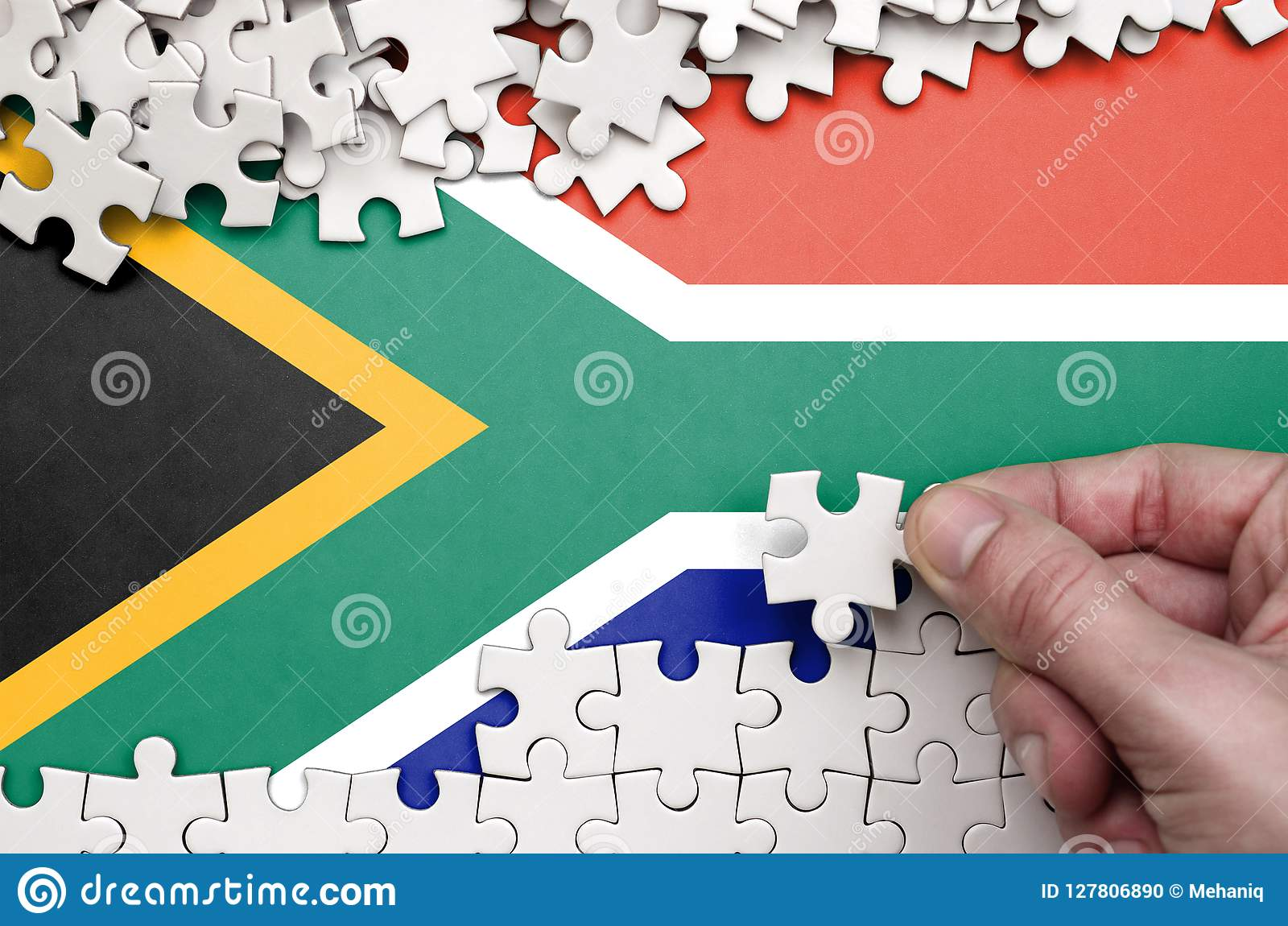 South Africa flag is depicted on a table on which the human hand folds a puzzle of white color