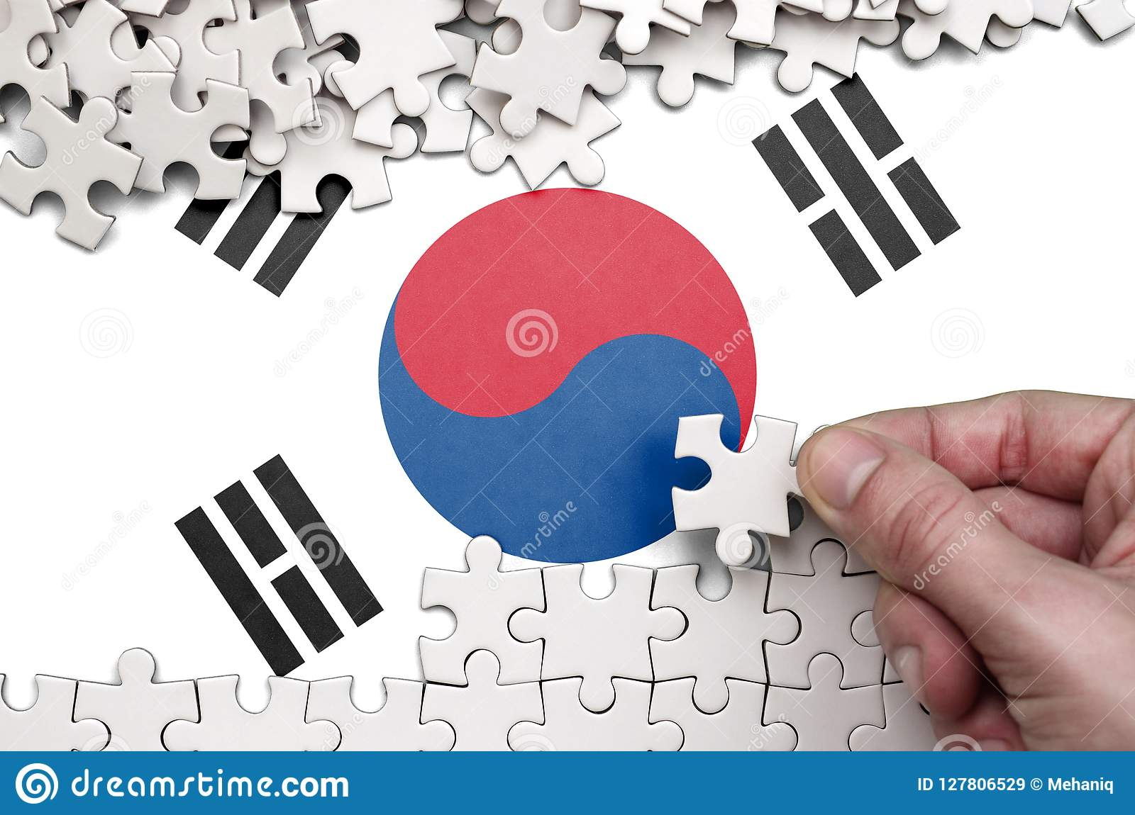 South Korea flag is depicted on a table on which the human hand folds a puzzle of white color