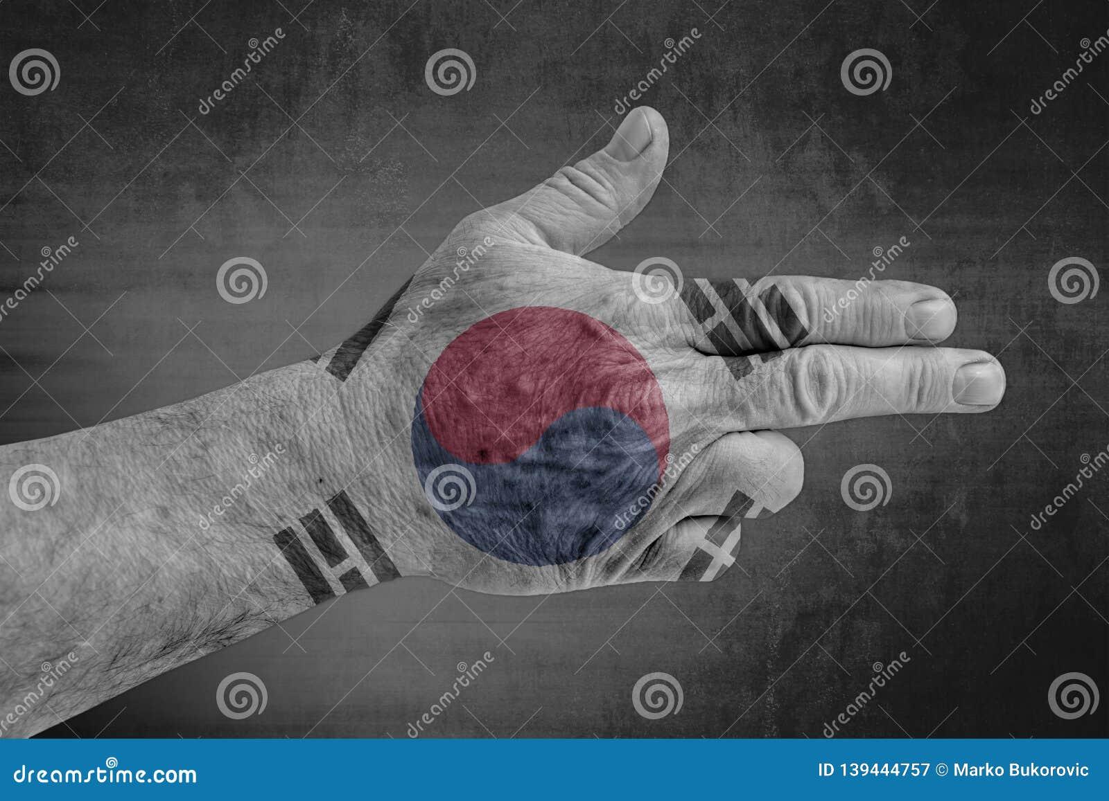 South Korea flag painted on male hand like a gun