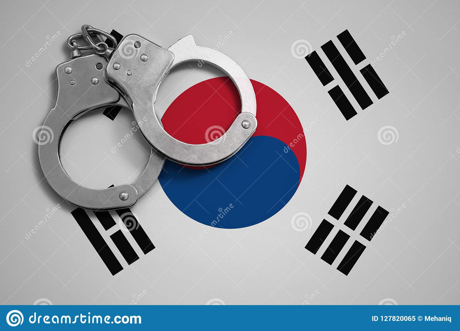 South Korea flag and police handcuffs. The concept of crime and offenses in the country