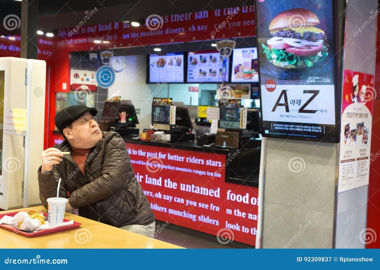 South Korean Man Sitting At A Fast Food Restaurant  Editorial