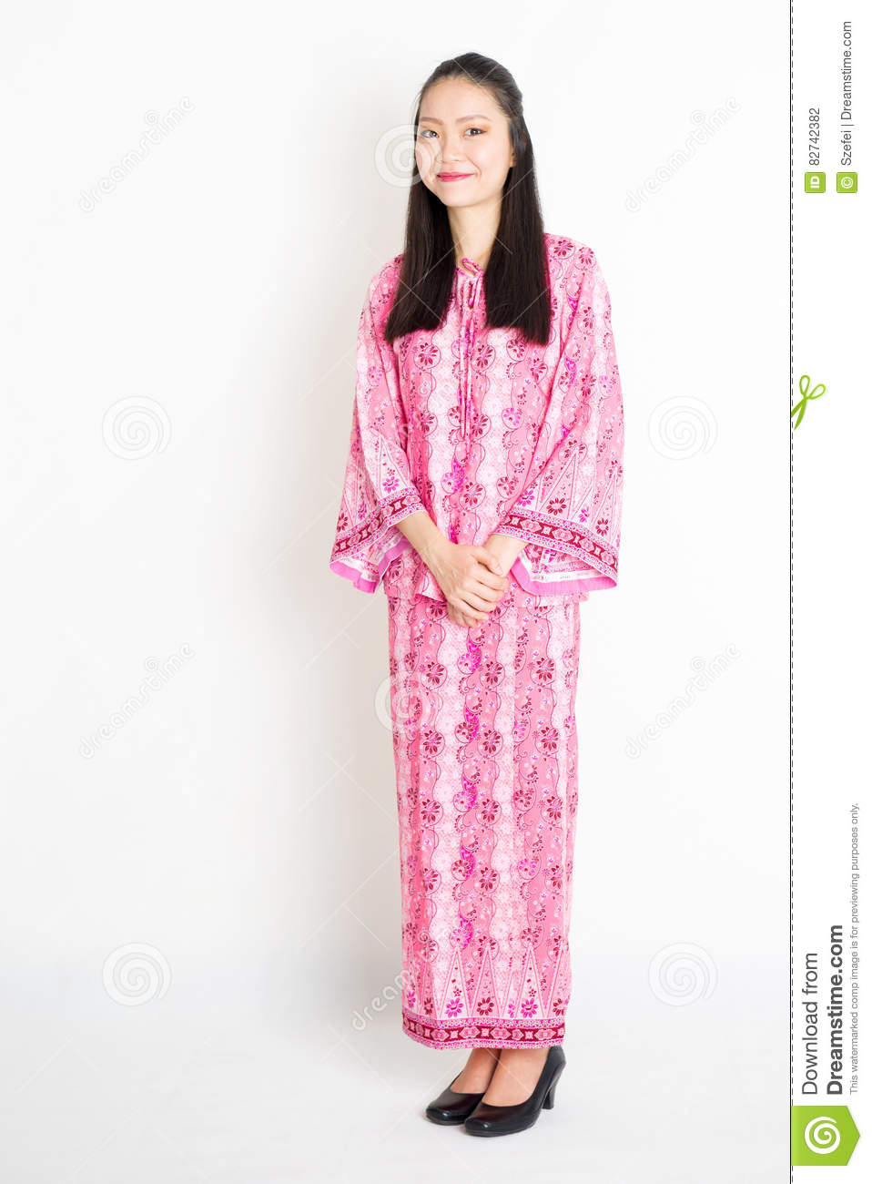 9196737dd Portrait of young southeast Asian woman in traditional Malay batik dress  smiling, standing on plain background.