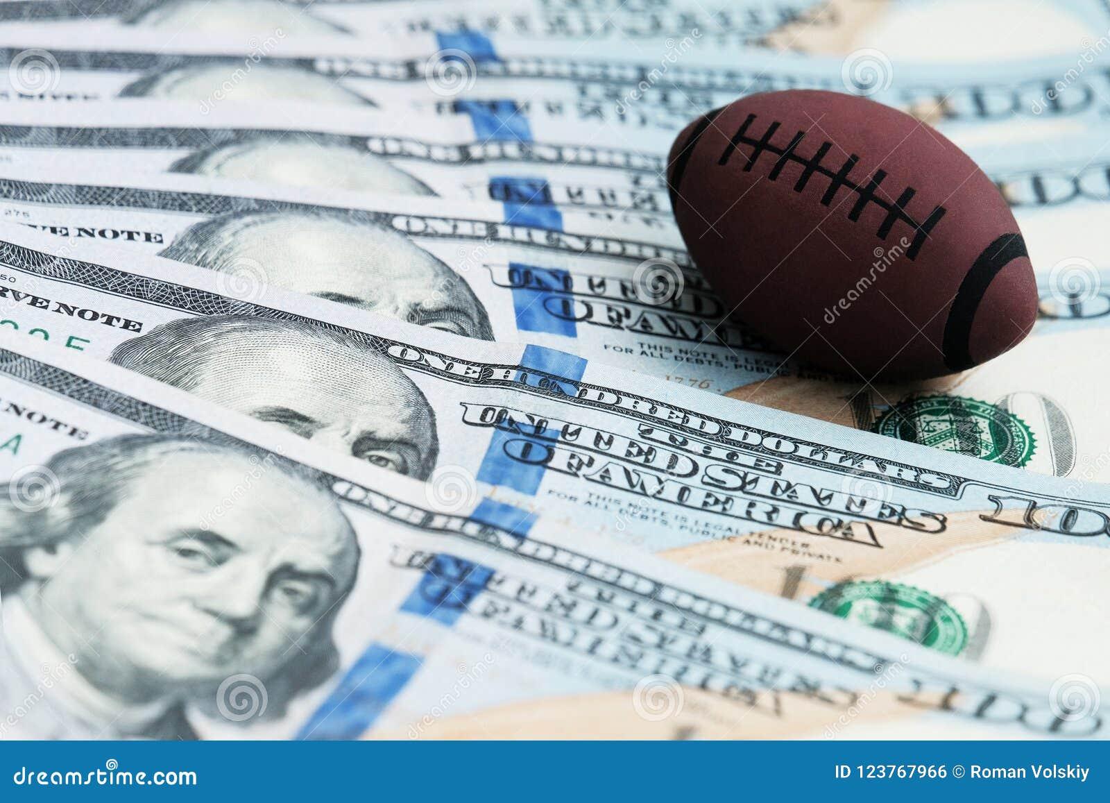 Souvenirboll för att spela rugby eller amerikansk fotboll på USA-sedlar Begreppet av att slå vad för korruption eller för sportar