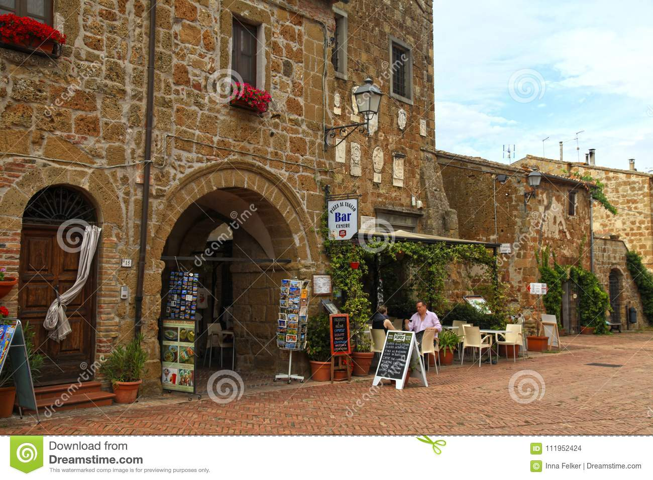 Tourists relax in outdoor cafe on central square of Sovana, Tuscany, Italy