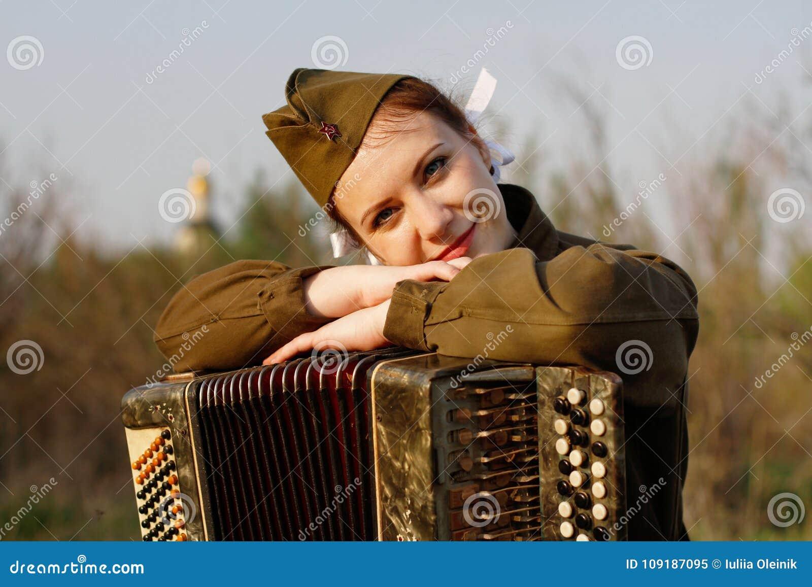 Sovjet vrouwelijke militair in eenvormig van Wereldoorlog II met een harmonika