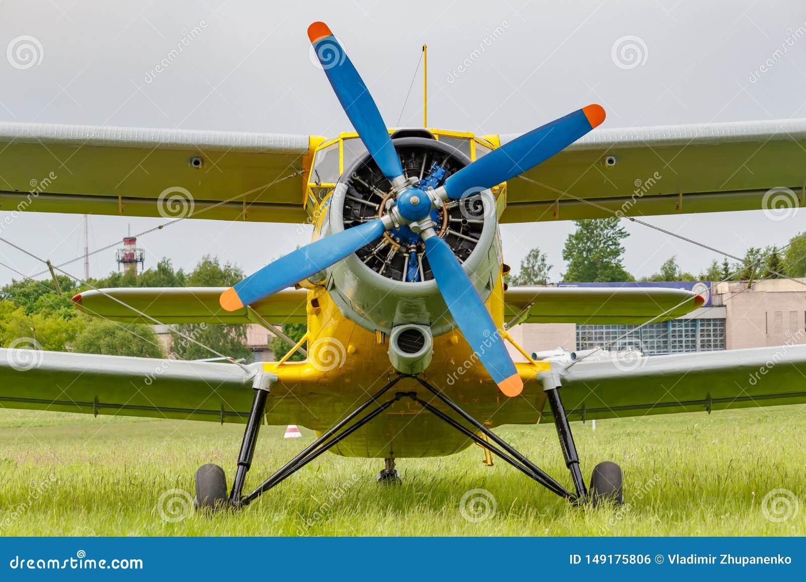 Sovjetvliegtuigentweedekker Antonov een-2 met blauwe vier bladpropeller en gele die fuselage op een groen gras van vliegveld word