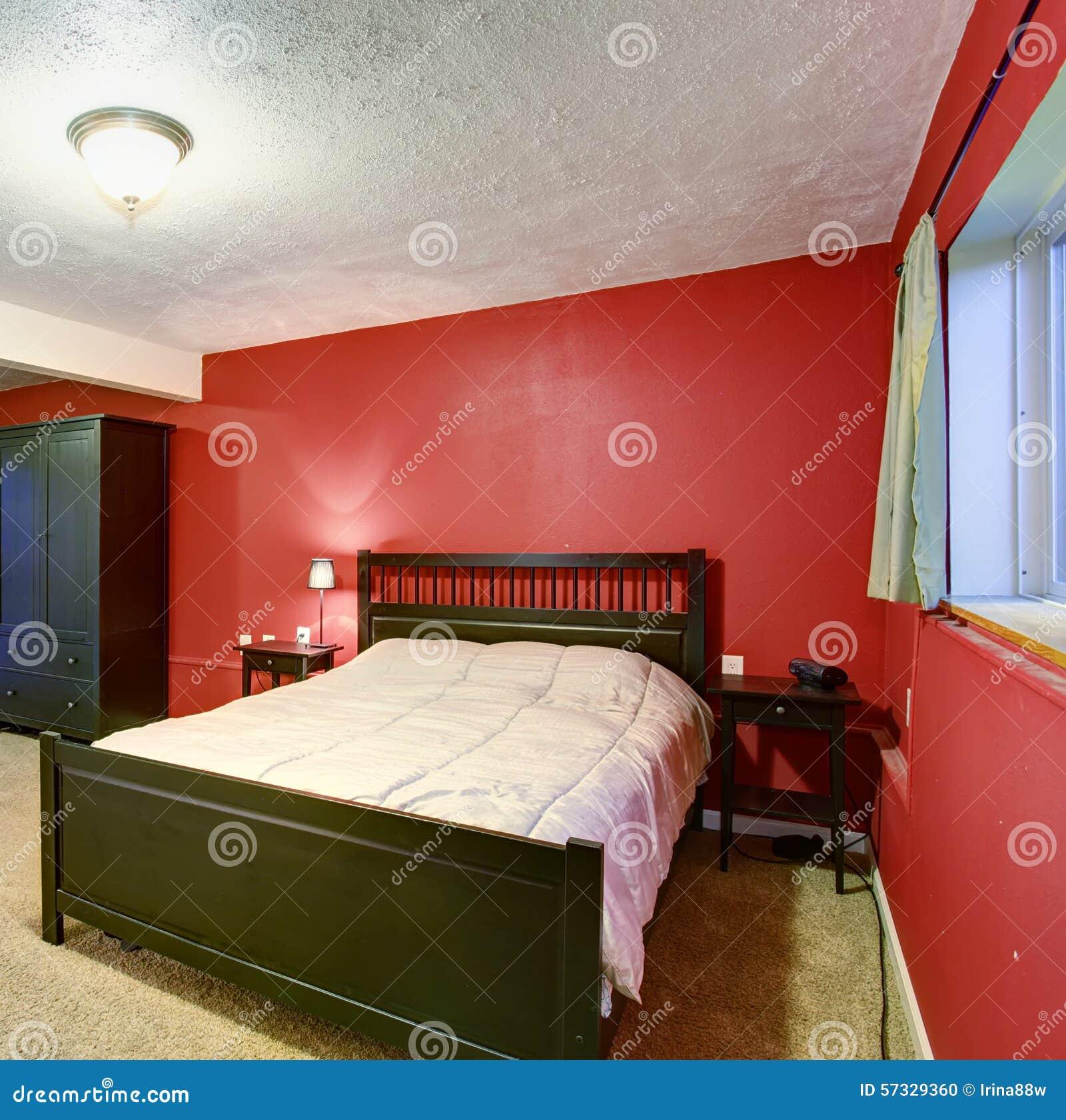 Sovrum med röda väggar svart färgmöblemang och beige filt ...