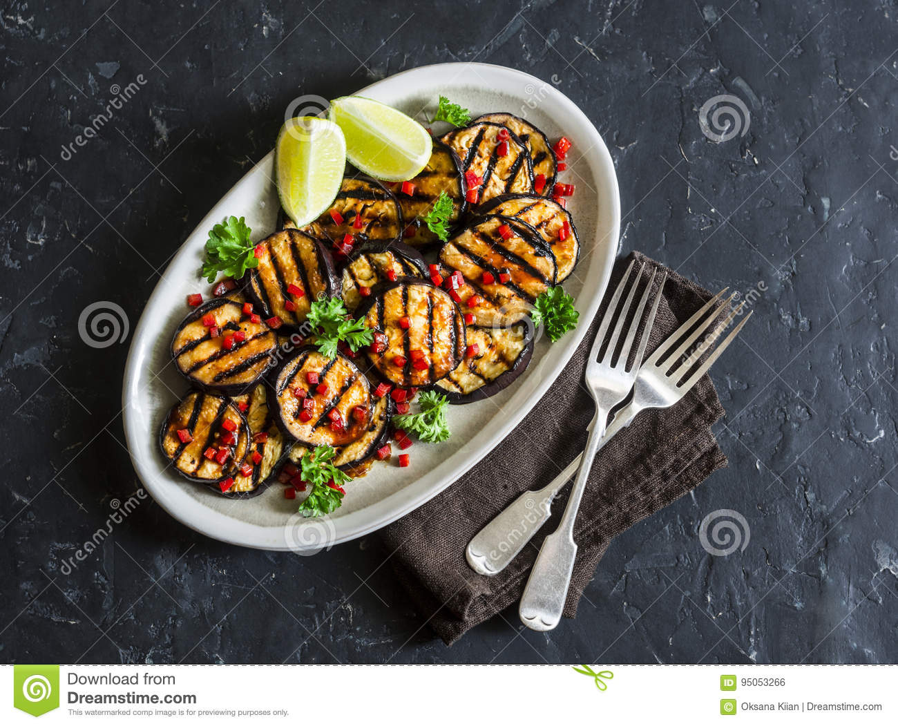 Soy sauce and ginger marinated grilled eggplant on a dark background, top view. Delicious vegetarian appetizer or snack.