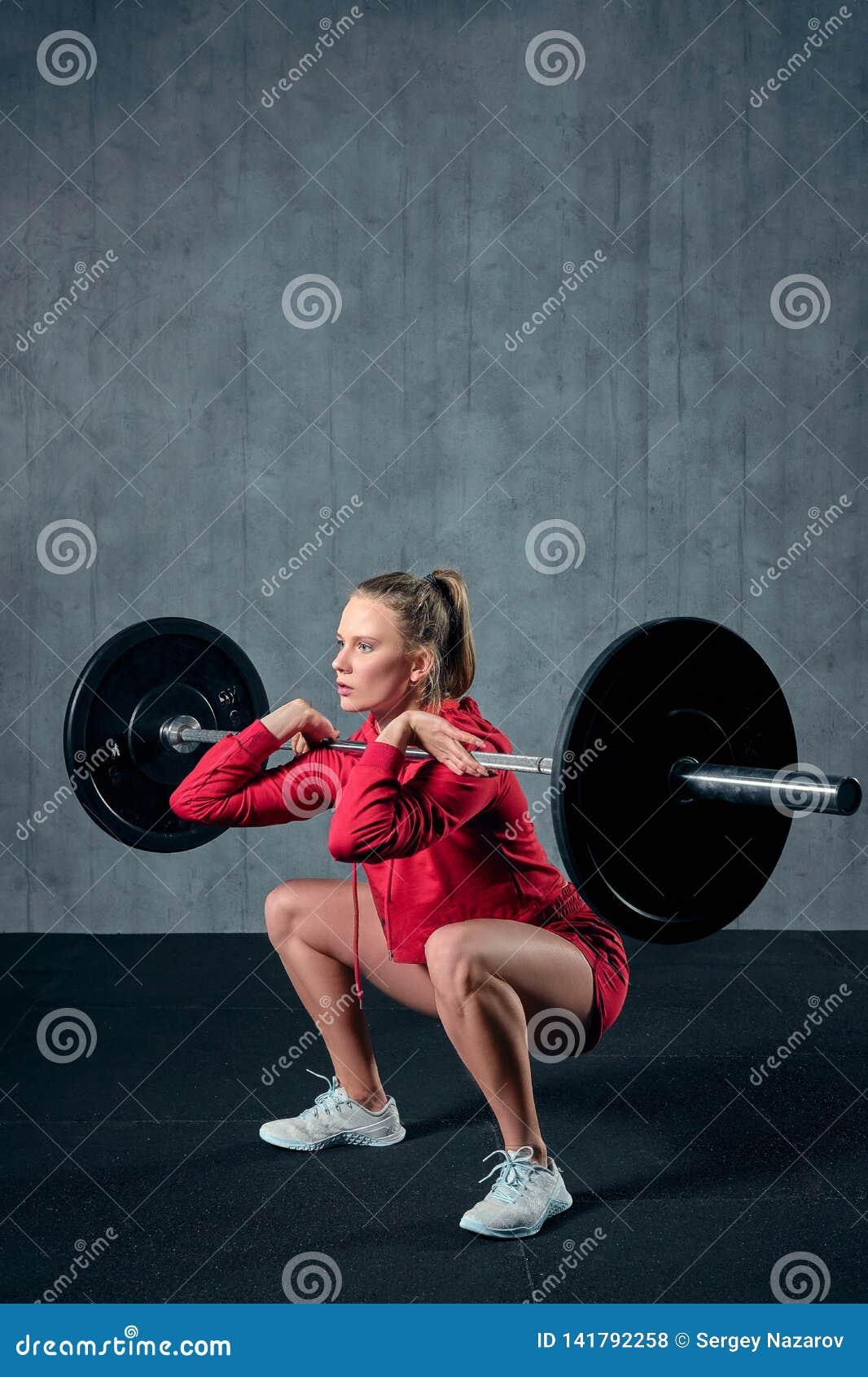 Spänd ung idrottskvinna som är klar att utföra skuldrapressövning med den tunga skivstången