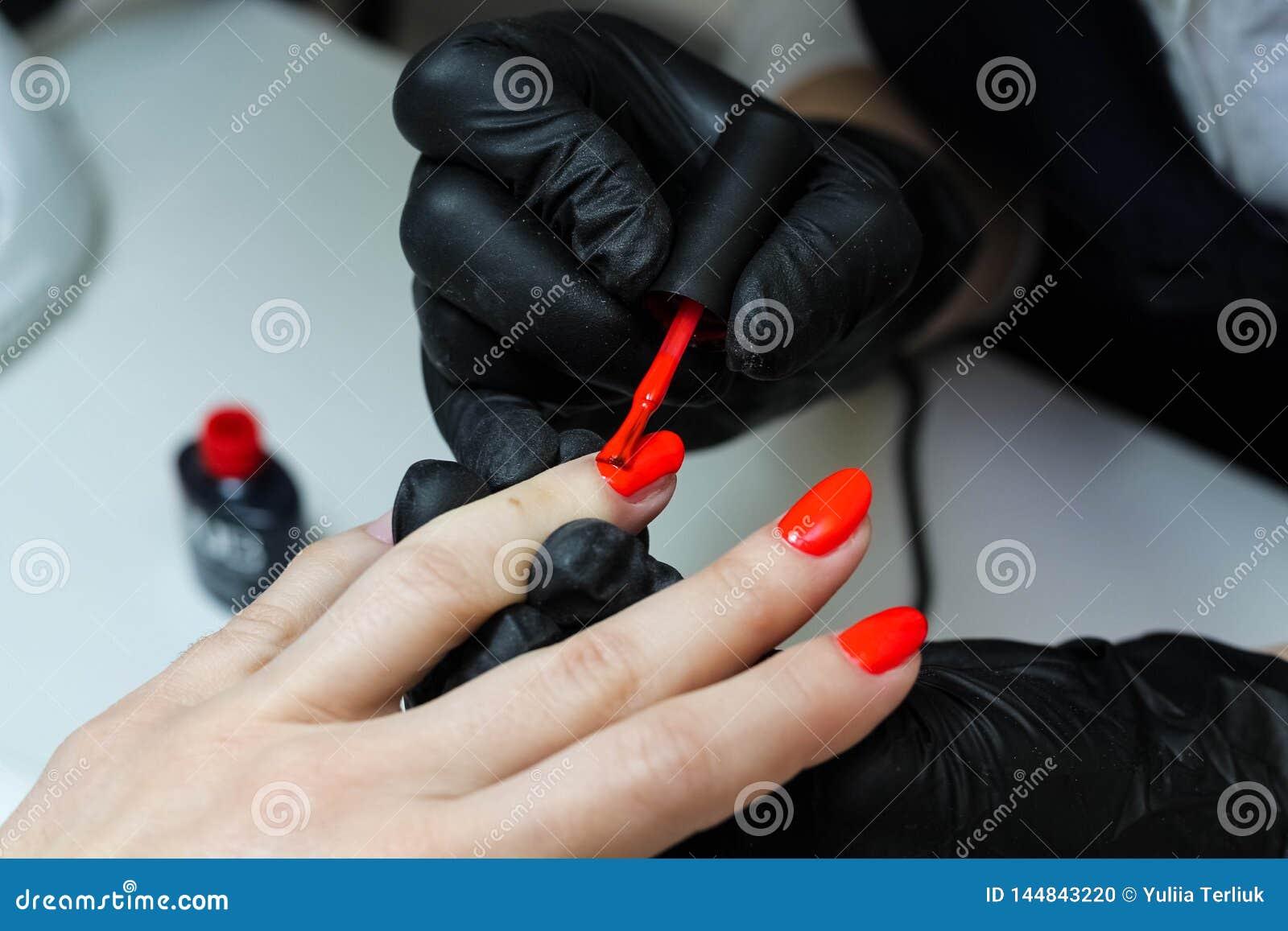 Sp?cialiste en manucure dans des soins noirs de gants au sujet des ongles de mains Le manucure peint des ongles avec le vernis ?