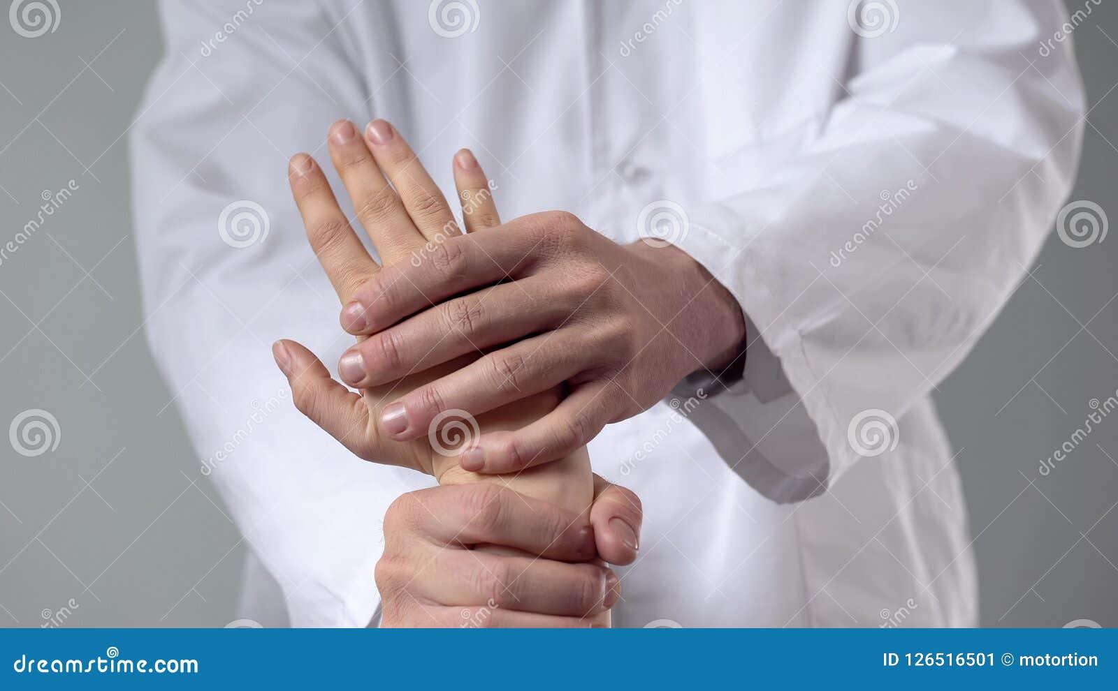 Spécialiste en soins de santé examinant le poignet blessé, traitement de médecine parallèle