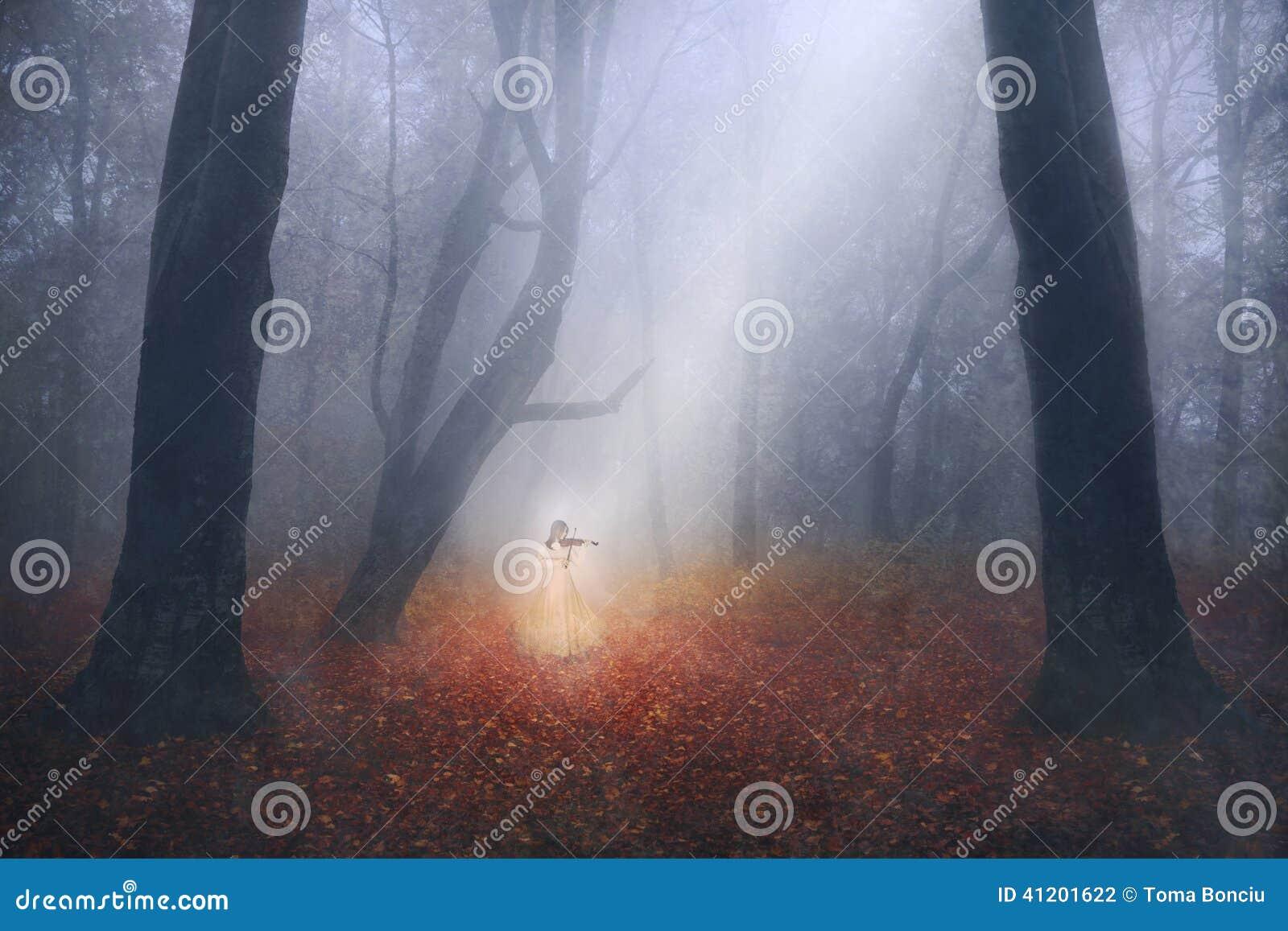 Spöklik flicka som spelar fiolen i en dimmig skog