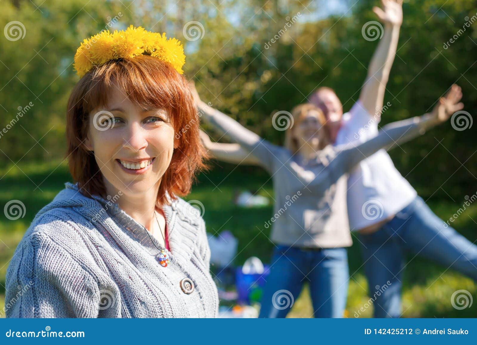 Spaßpicknick mit Freunden Ein Kranz des Löwenzahns auf seinem Kopf