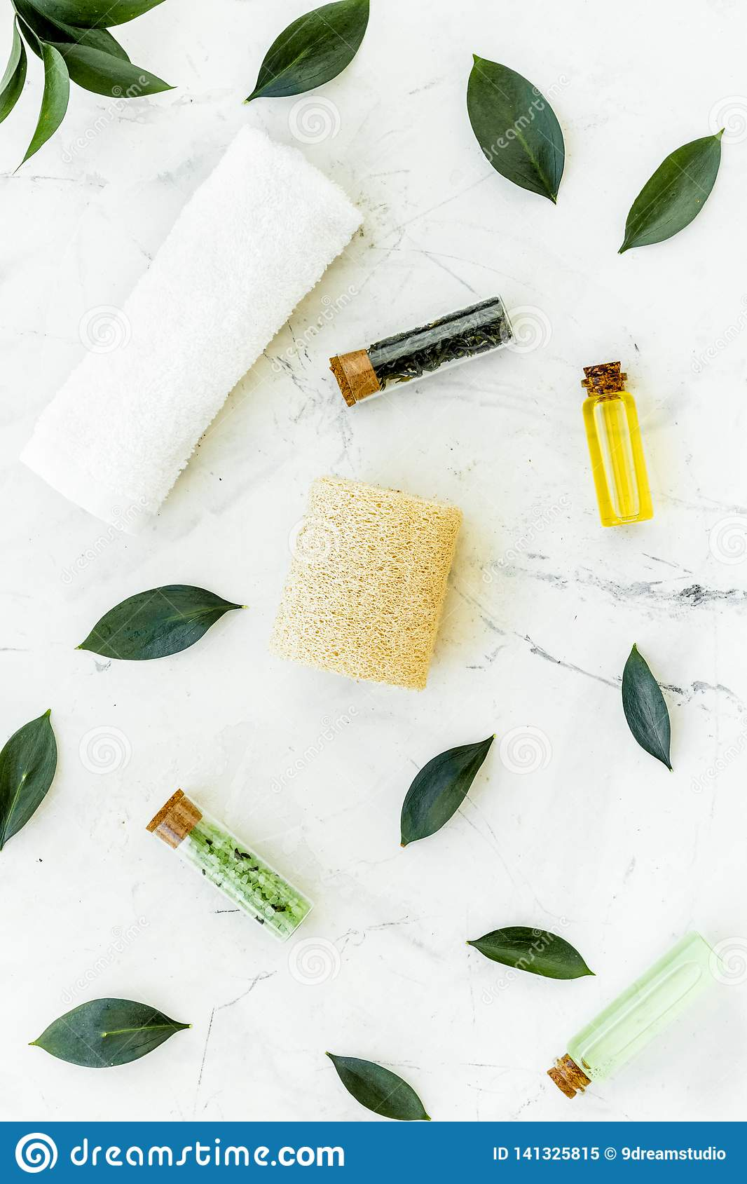 Spa composition with essential tea tree oil. Fresh tea tree leaves, natural cosmetics, towel on white stone background
