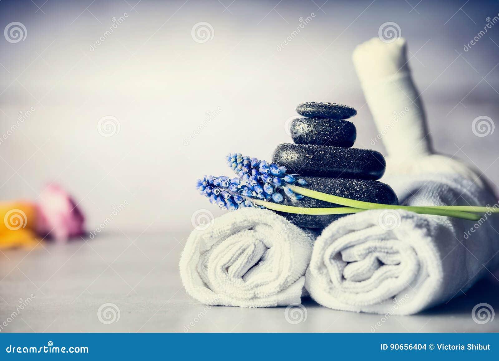 Spa massageinställning med handdukar, varma stenar och blåa blommor, slut upp, wellnessbegrepp
