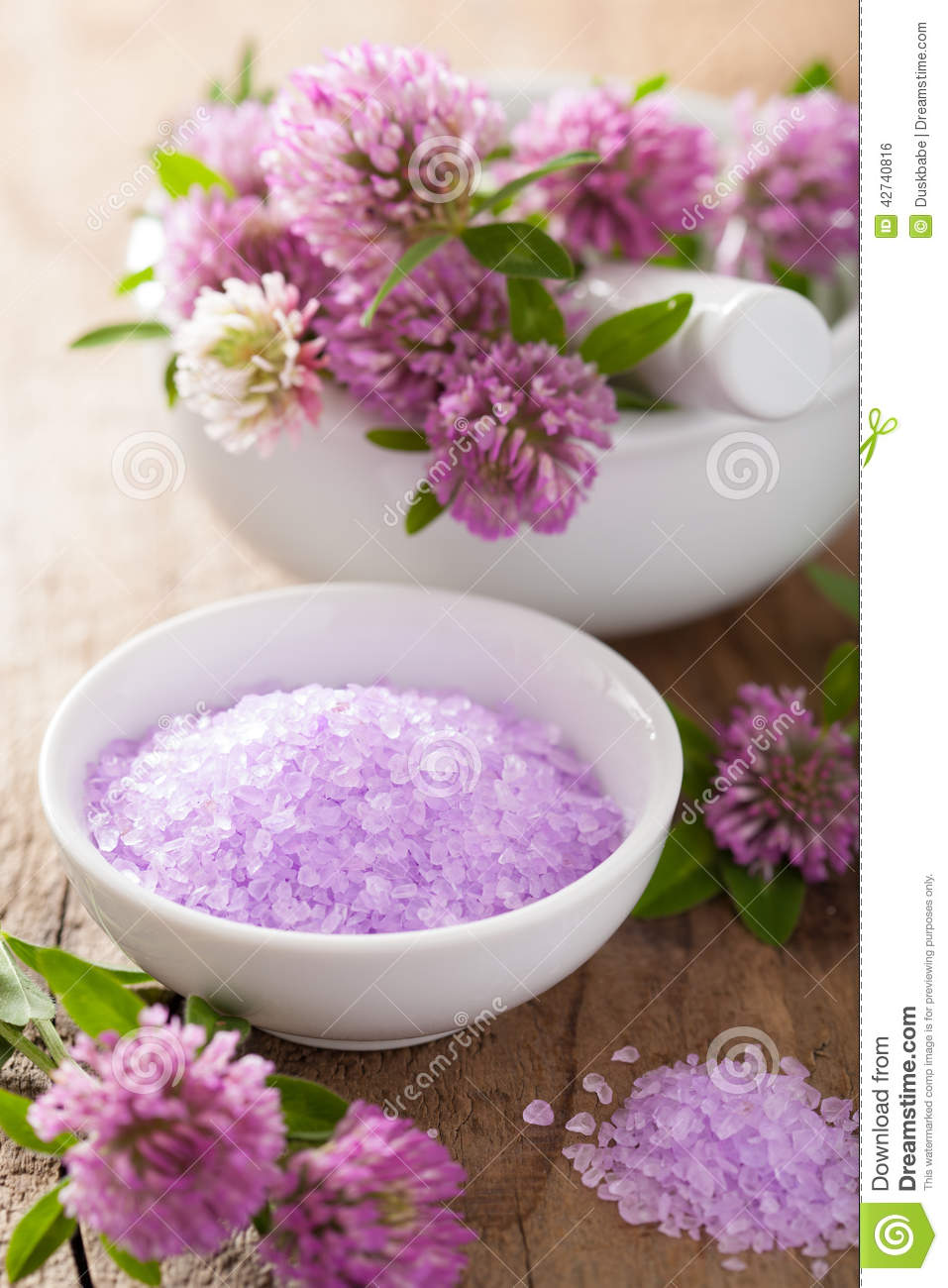 spa with purple herbal salt and clover flowers stock photo