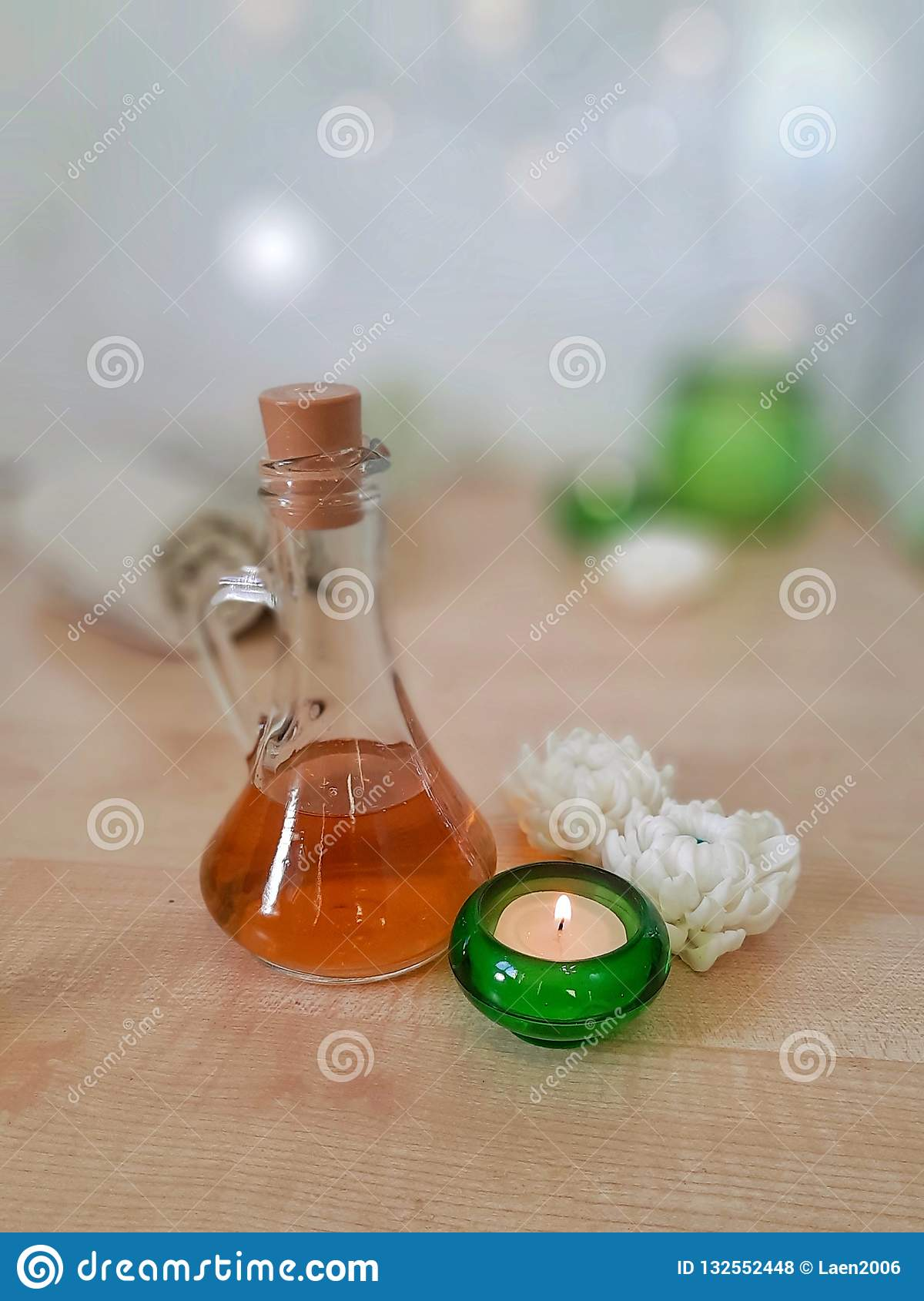 Spa aromatherapy concept. Towel, essential oil, handmade flower soap, burning candle in green glass on wooden table