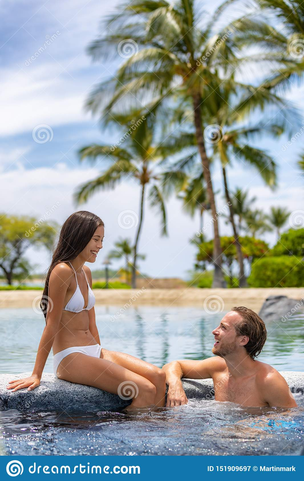 Spa resort couple relaxing enjoying jacuzzi hot tub swimming pool outdoors on summer vacation travel holidays honeymoon getaway.