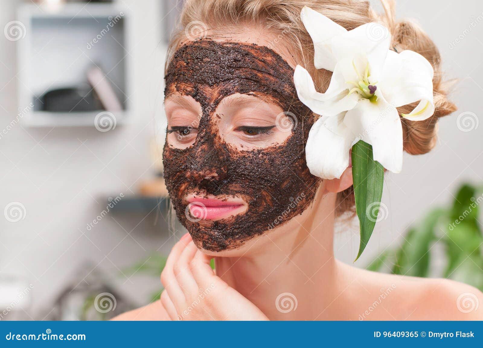 Spa salon. Beautiful woman with coffee facial mask at beauty salon