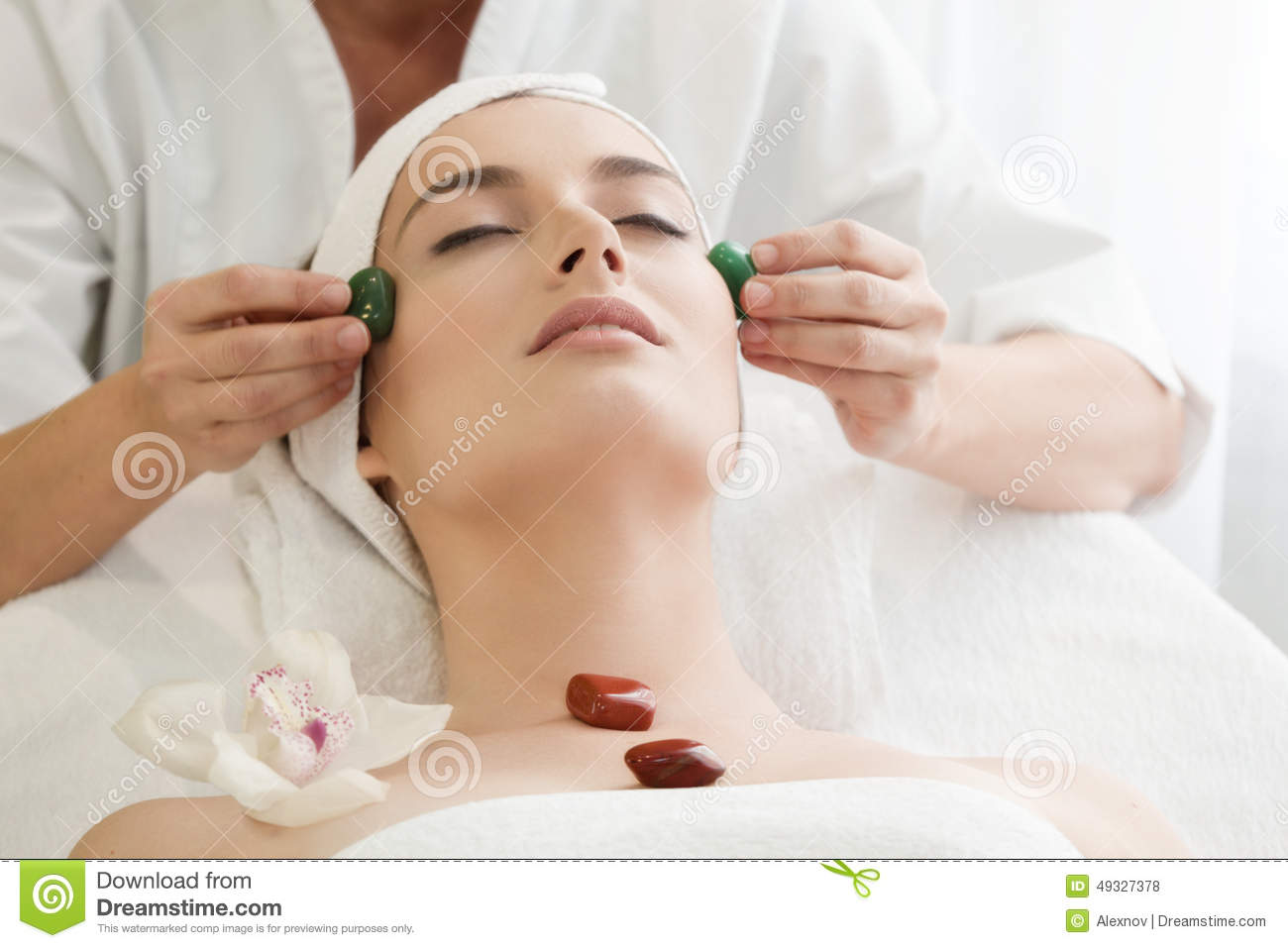 Spa salon: Young Beautiful Woman Having Facial Massage with Stones .