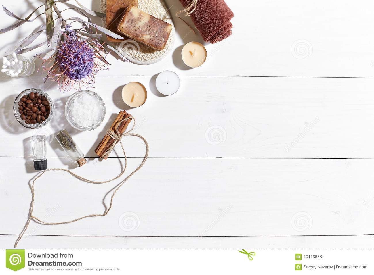 Spa set with sea salt, essential oil, soap and towel decorated with dry flower on white wooden background