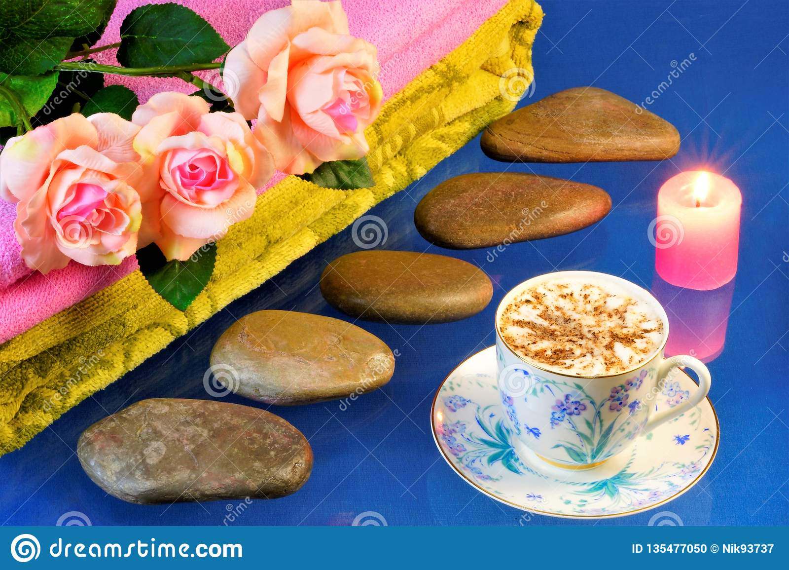 Spa stones, beautiful roses, candle and coffee. Hot stone massage-stone therapy, effective treatment for many diseases. On a blue