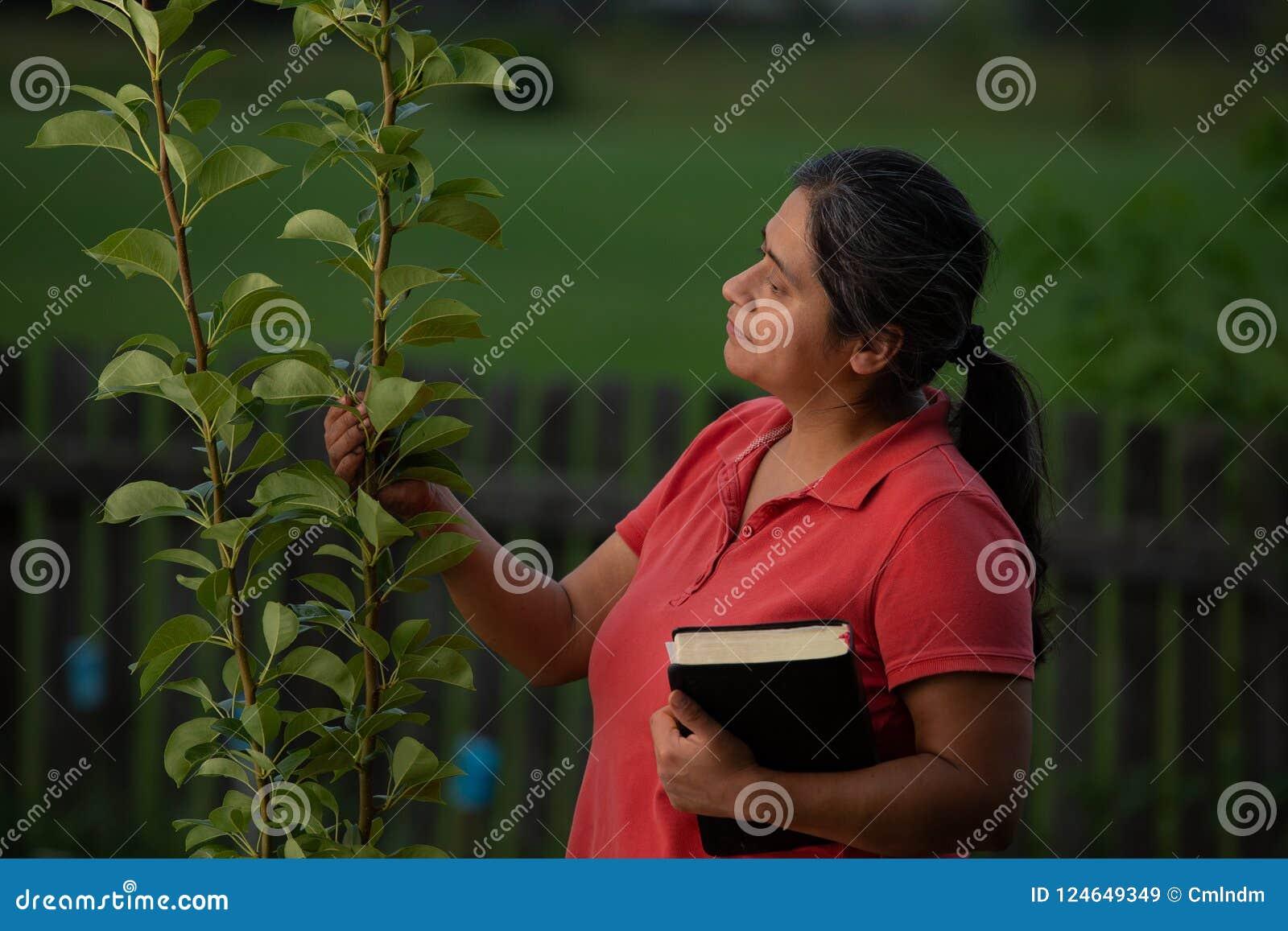 Spaans Christian Woman Contemplating haar Perenboom na het Werken van Haar Werf en het Hebben van Meditatie