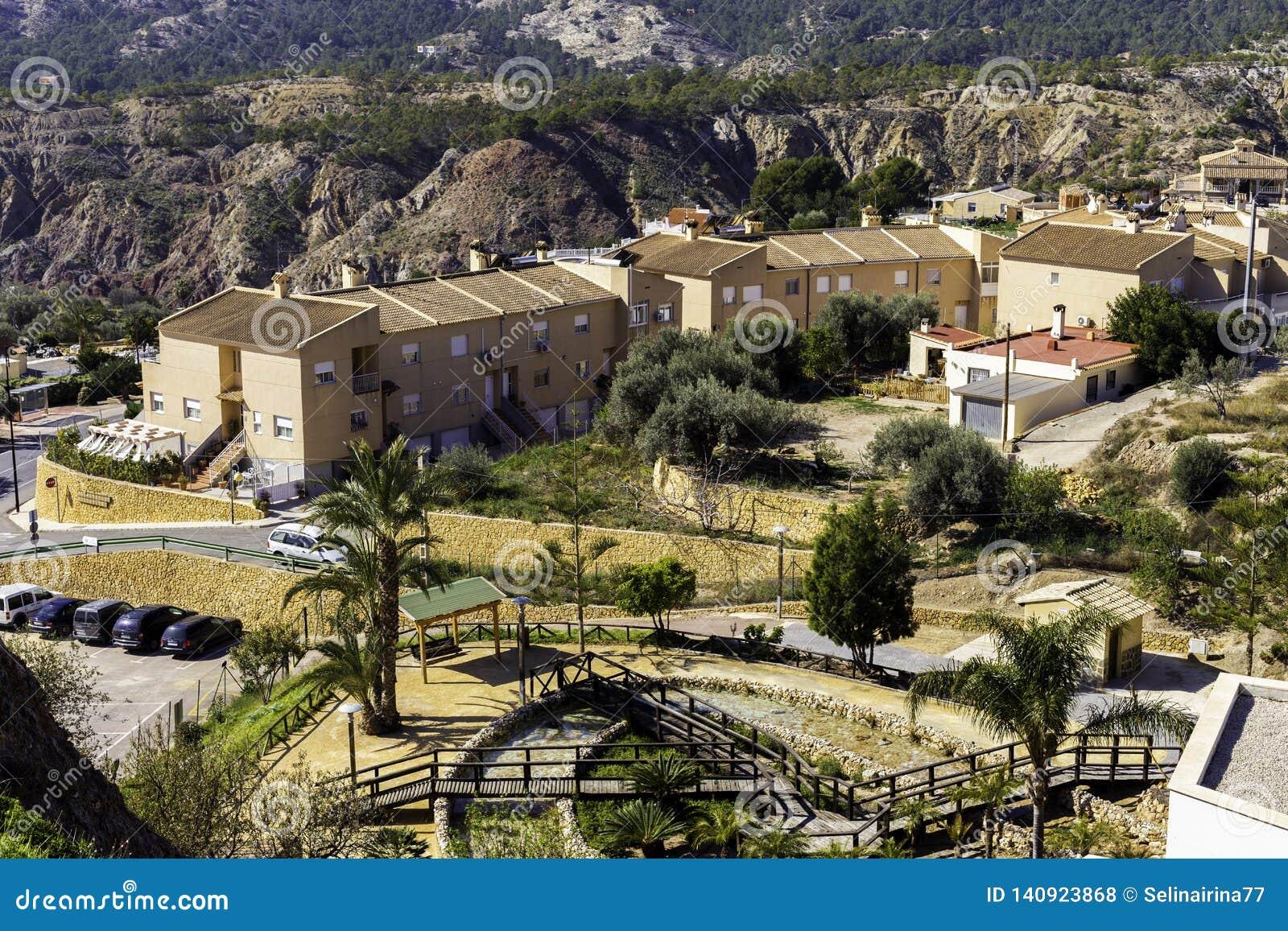 Spaans dorp met huizen, parkeren en gebied voor rust en gangen bij de voet bergen, Fenistrat Spanje
