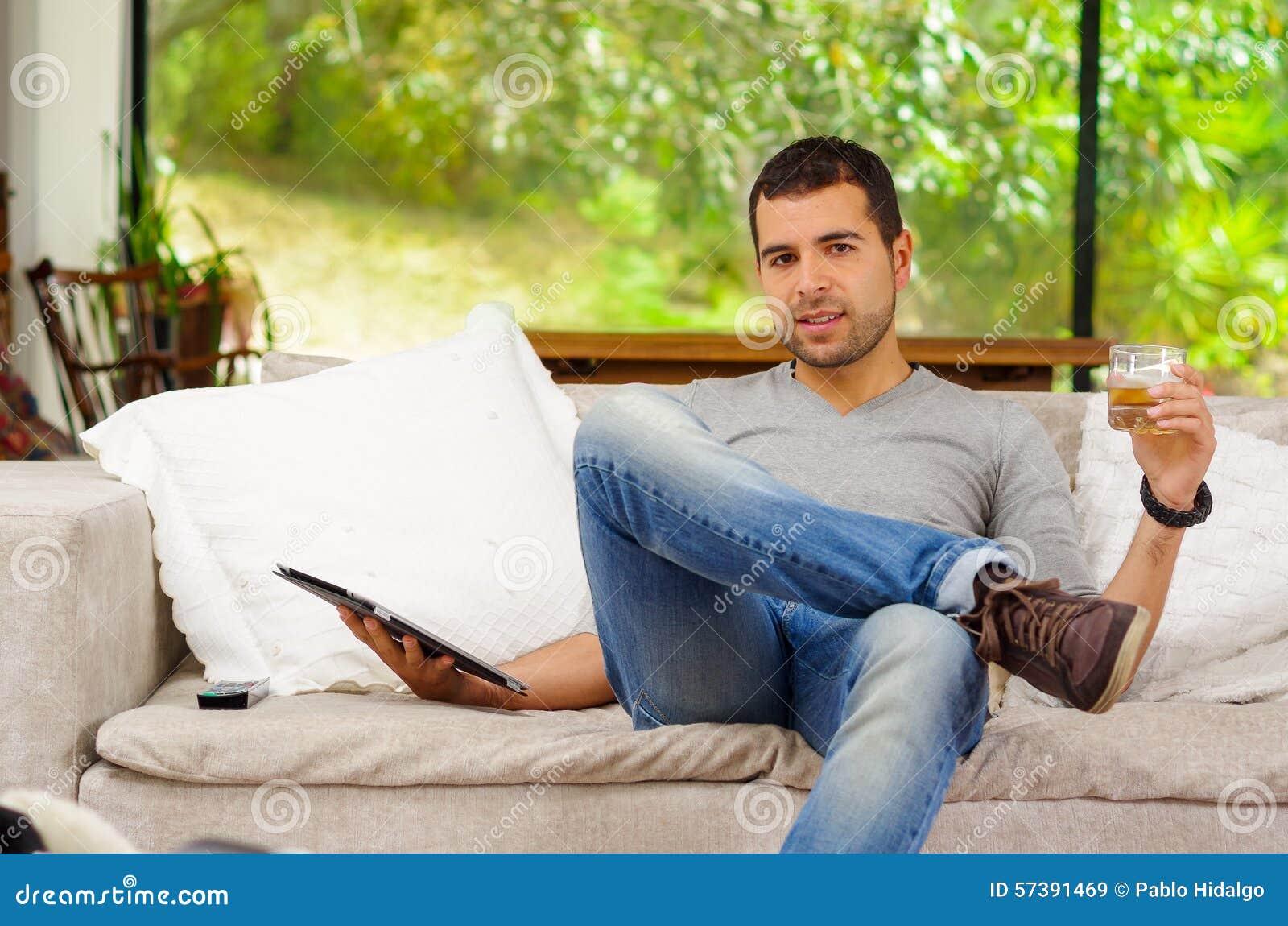 Spaanse mens die denimjeans en grijze sweater dragen