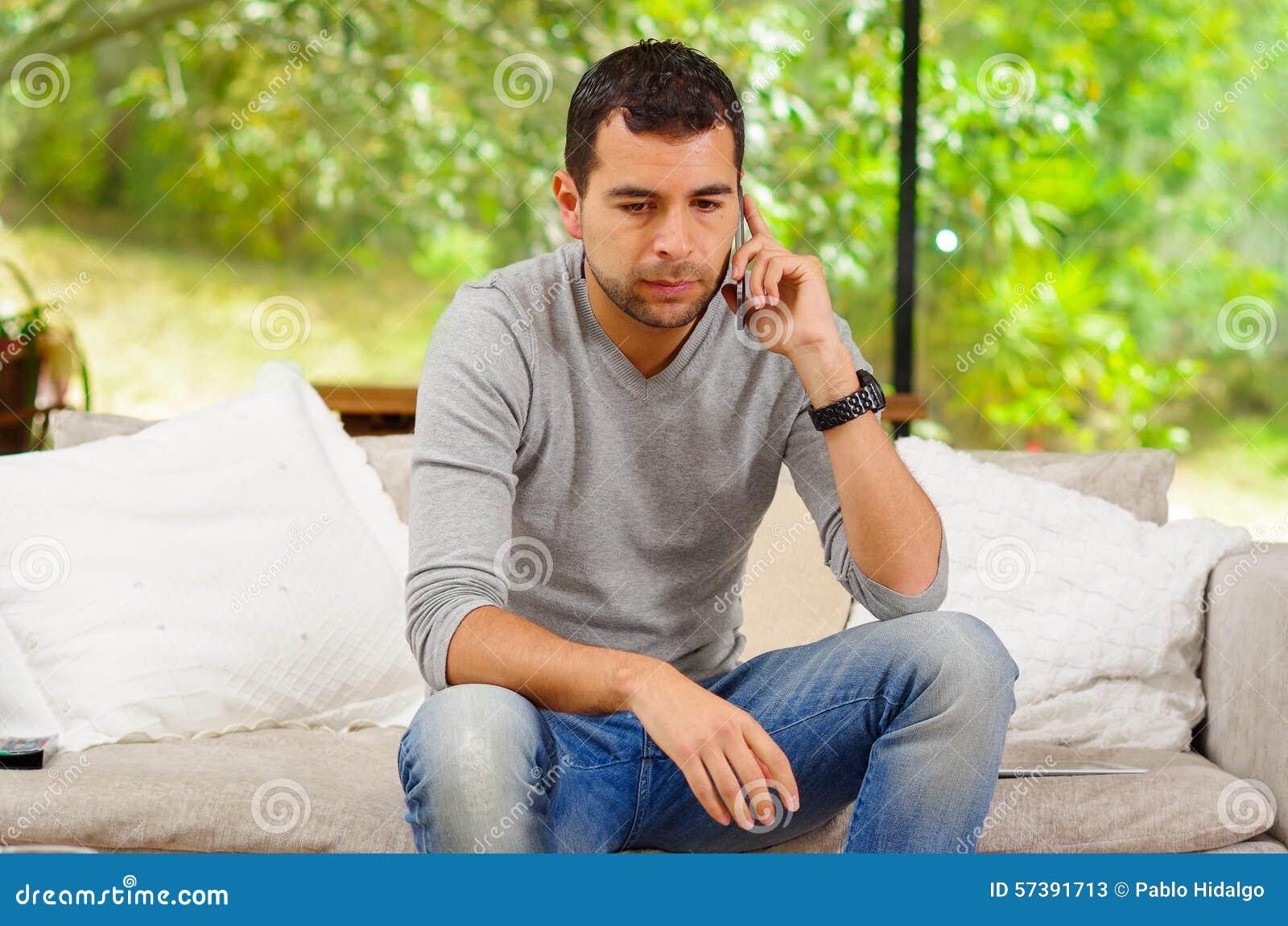 Spaanse mens die denimjeans met grijze sweater dragen
