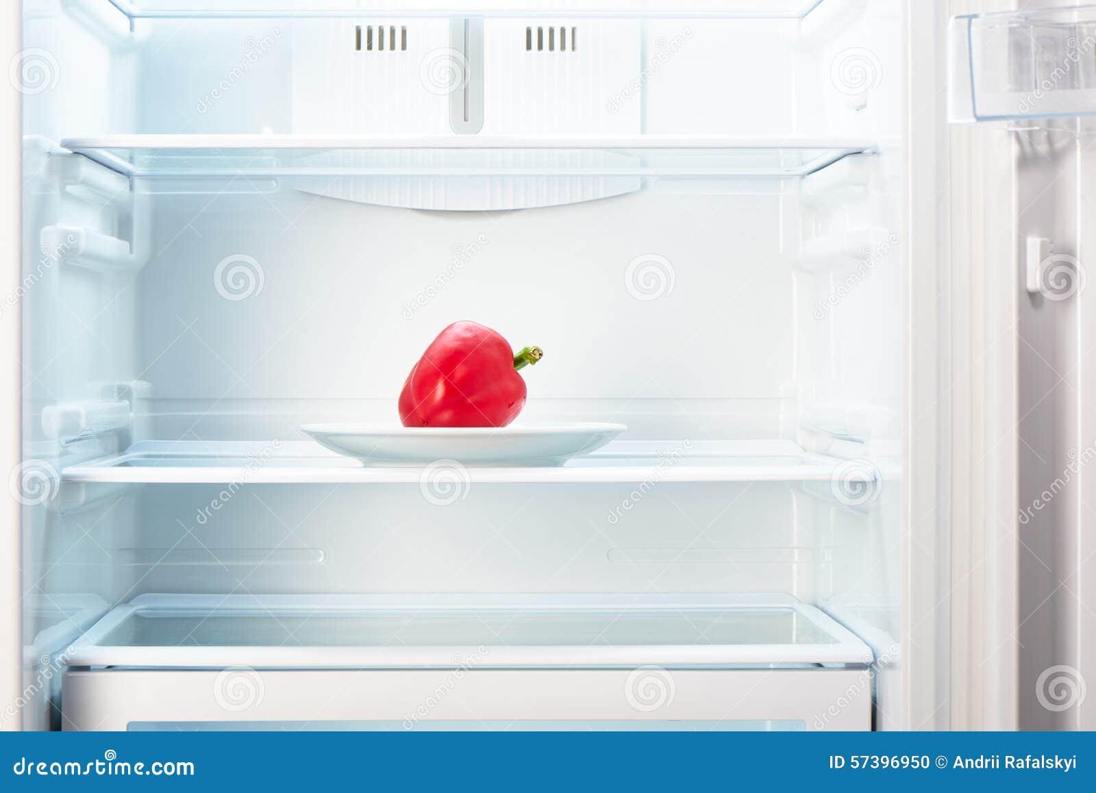 Spaanse peper op witte plaat in open lege ijskast