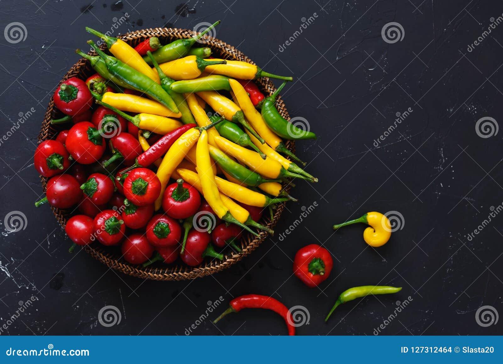 Spaanse peperpeper in kom tegen rustieke zwarte achtergrond