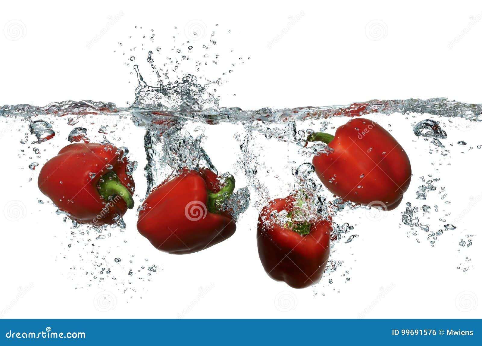 Spaanse pepers die in vers schoon water bespatten