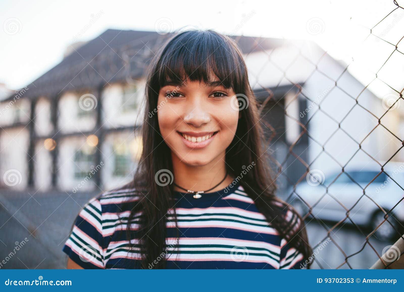 Spaanse vrouw die camera en het glimlachen bekijken