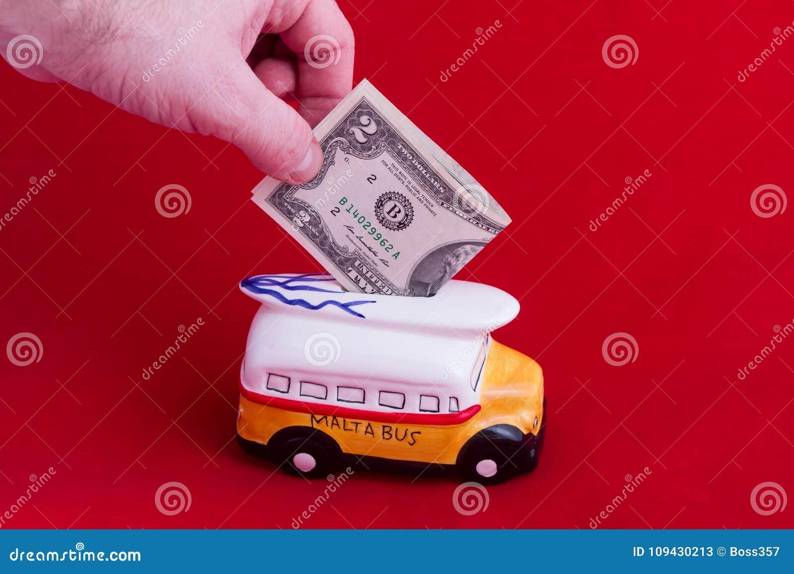 Spaarpot, in de vorm van een ceramische bus met een benaming van twee dollars, op een rode achtergrond Het concept besparingsgeld